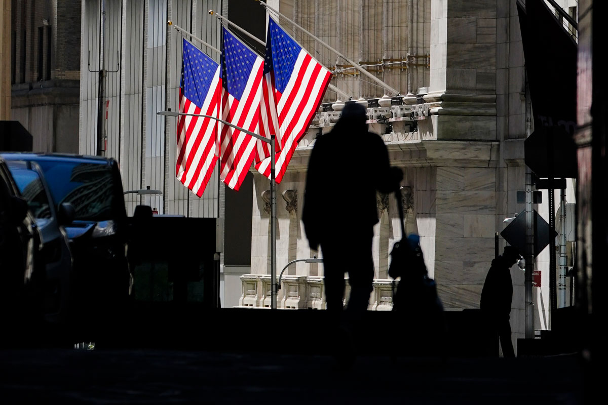 Pedestrians pass the New York Stock Exchange on Wednesday, October 14, in New York.