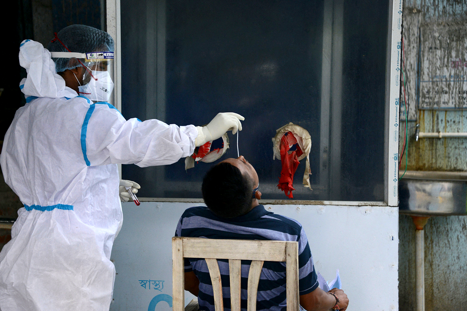 A health worker collects nasal swab for a Covid-19 coronavirus RT PCR test at the North Bengal Medical College and Hospital on the outskirts of Siliguri, India, on May 13.