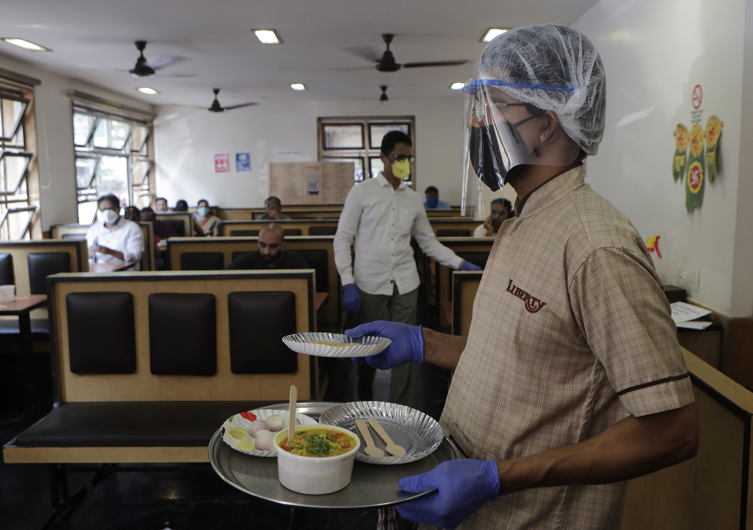 A waiter serves food to customers at a hotel in Mumbai, India, on Monday, October 5.