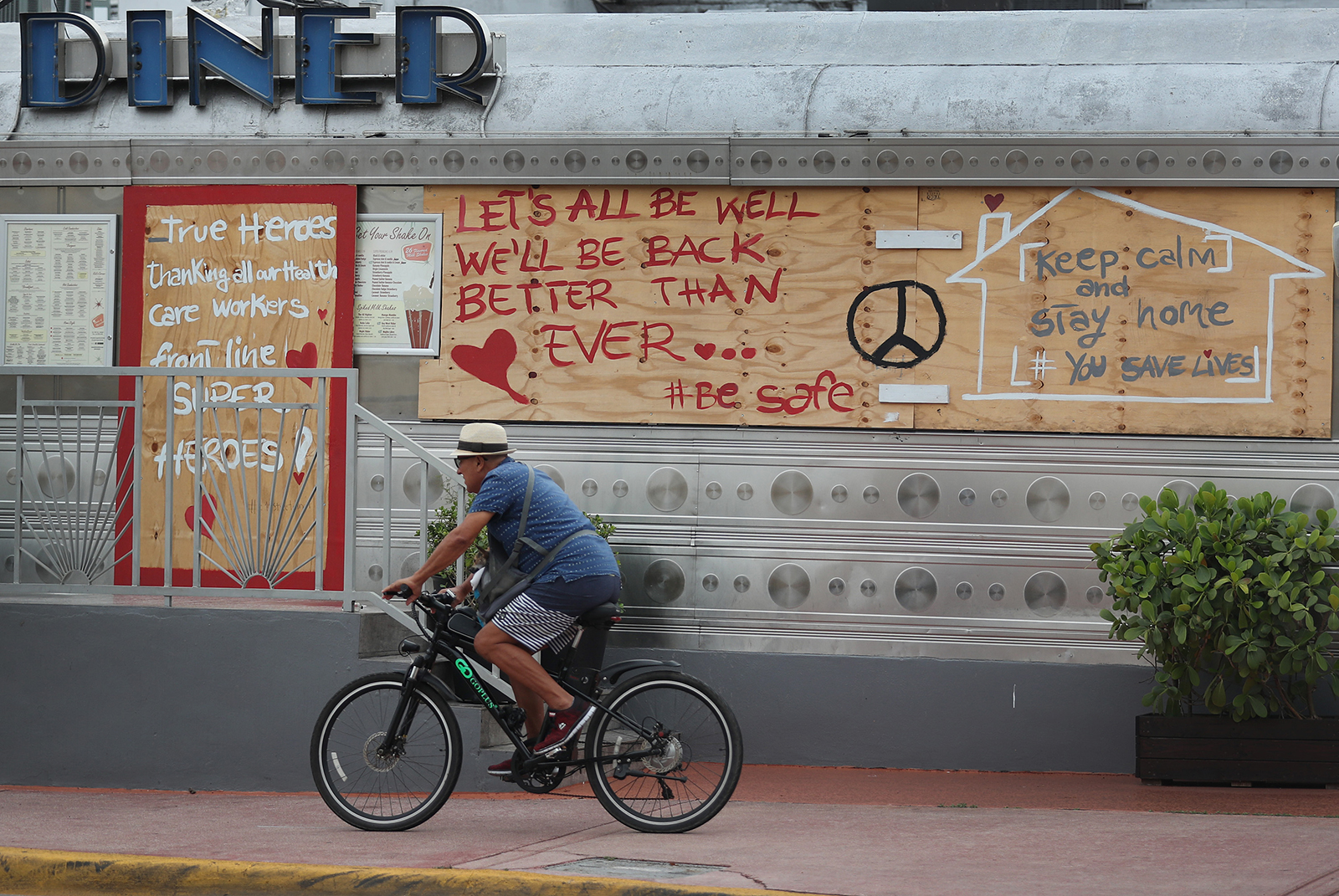 A bicyclist passes a restaurant with positive message about dealing with the coronavirus pandemic written on it on May 10, in Miami Beach, Florida.