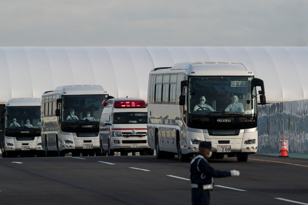 Buses carrying passengers who disembarked the quarantined Diamond Princess cruise ship and emergency vehicles at the Daikoku Pier on February 19, 2020 in Yokohama, Japan.