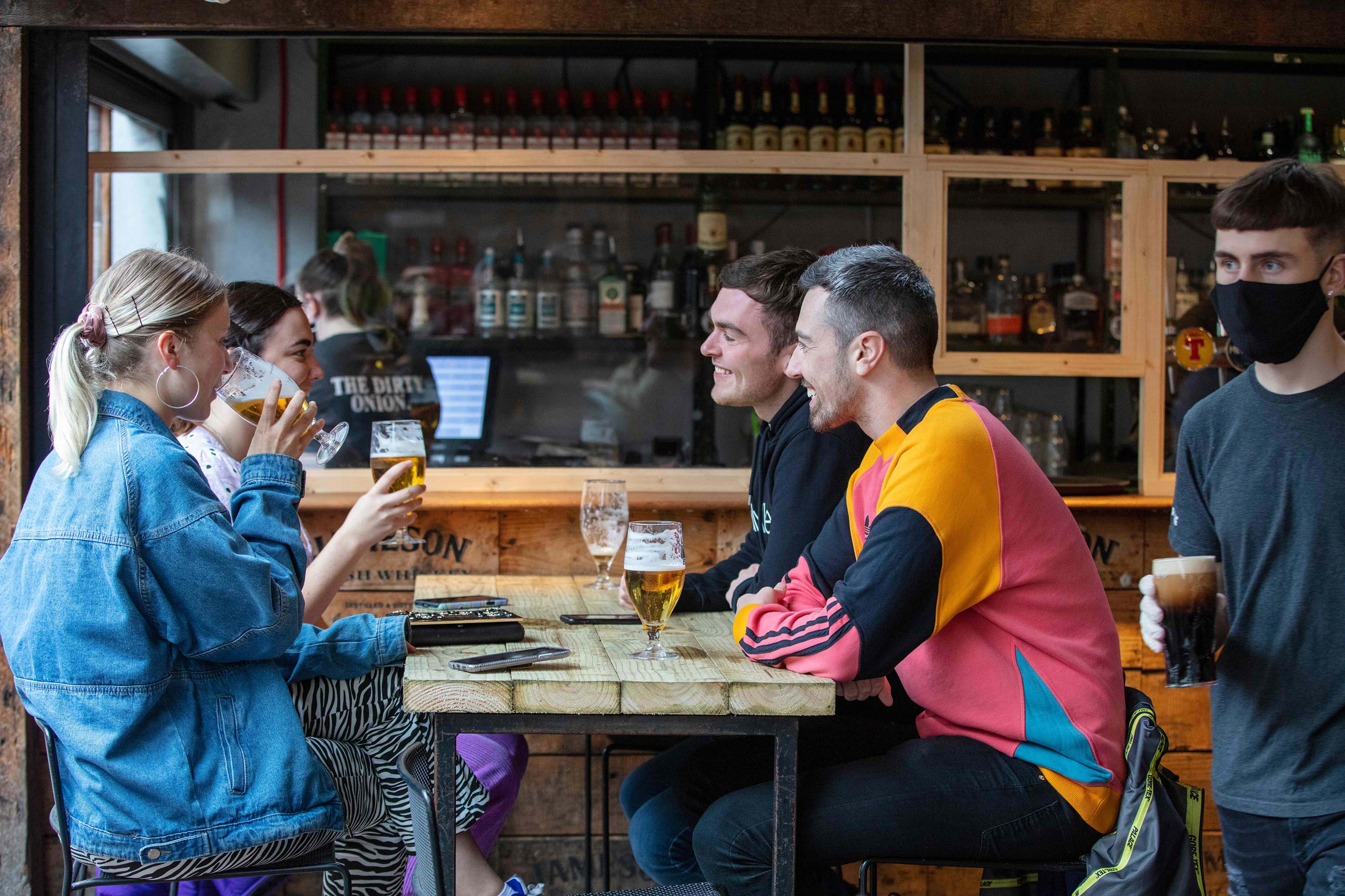 People socialize at the Dirty Onion Bar & Restaurant in Belfast on July 3, as pubs reopened their doors following the enforced closure due to the coronavirus pandemic.
