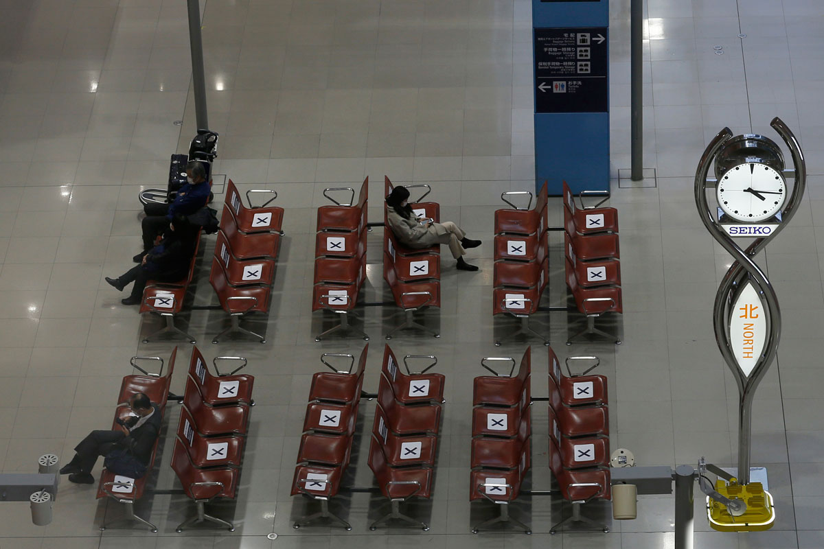 Passengers sit in an almost empty arrival hall at Kansai International Airport on December 27 in Osaka, Japan.