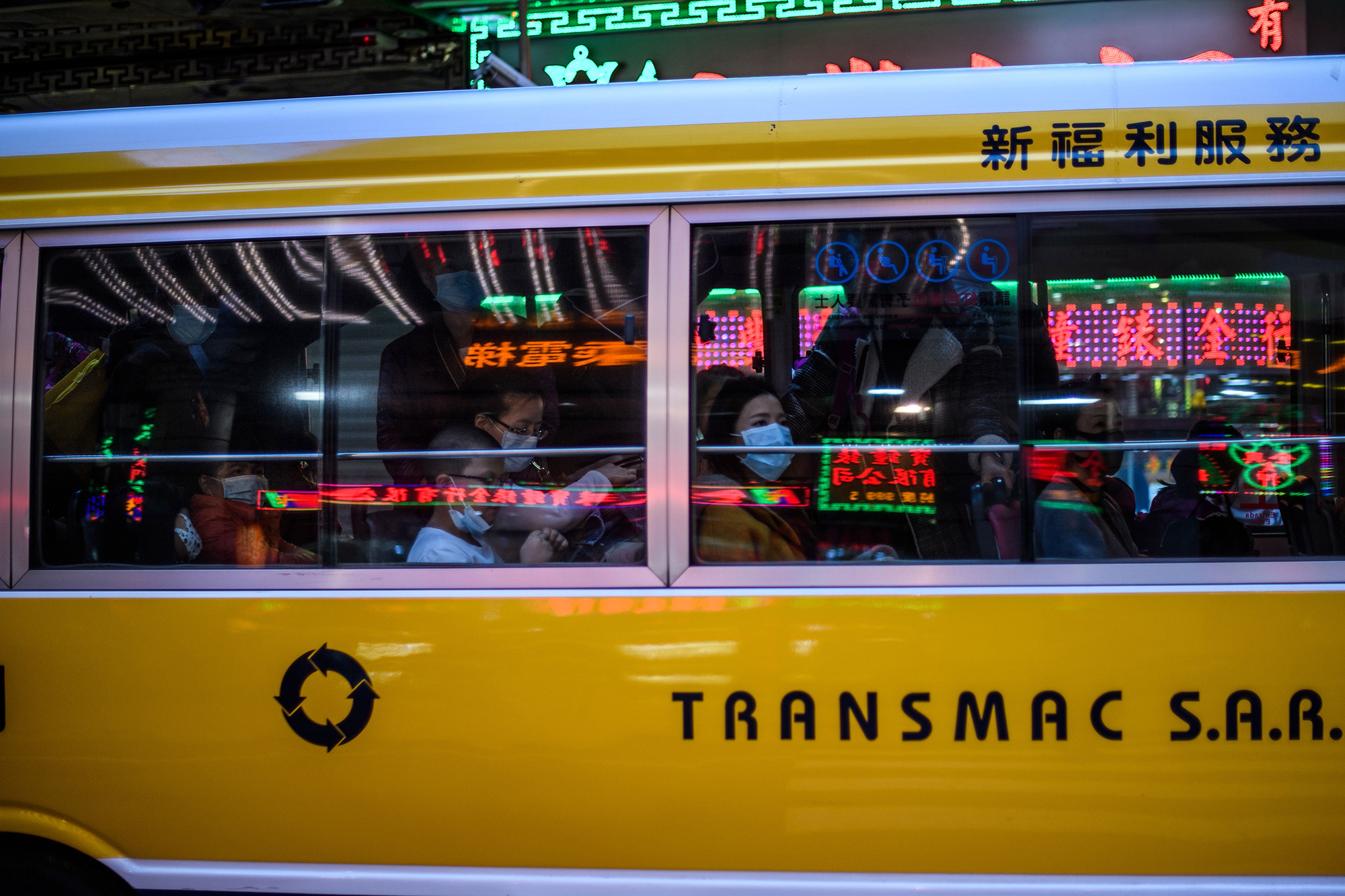 Commuters wear face masks as they travel in a bus in Macau on Wednesday.