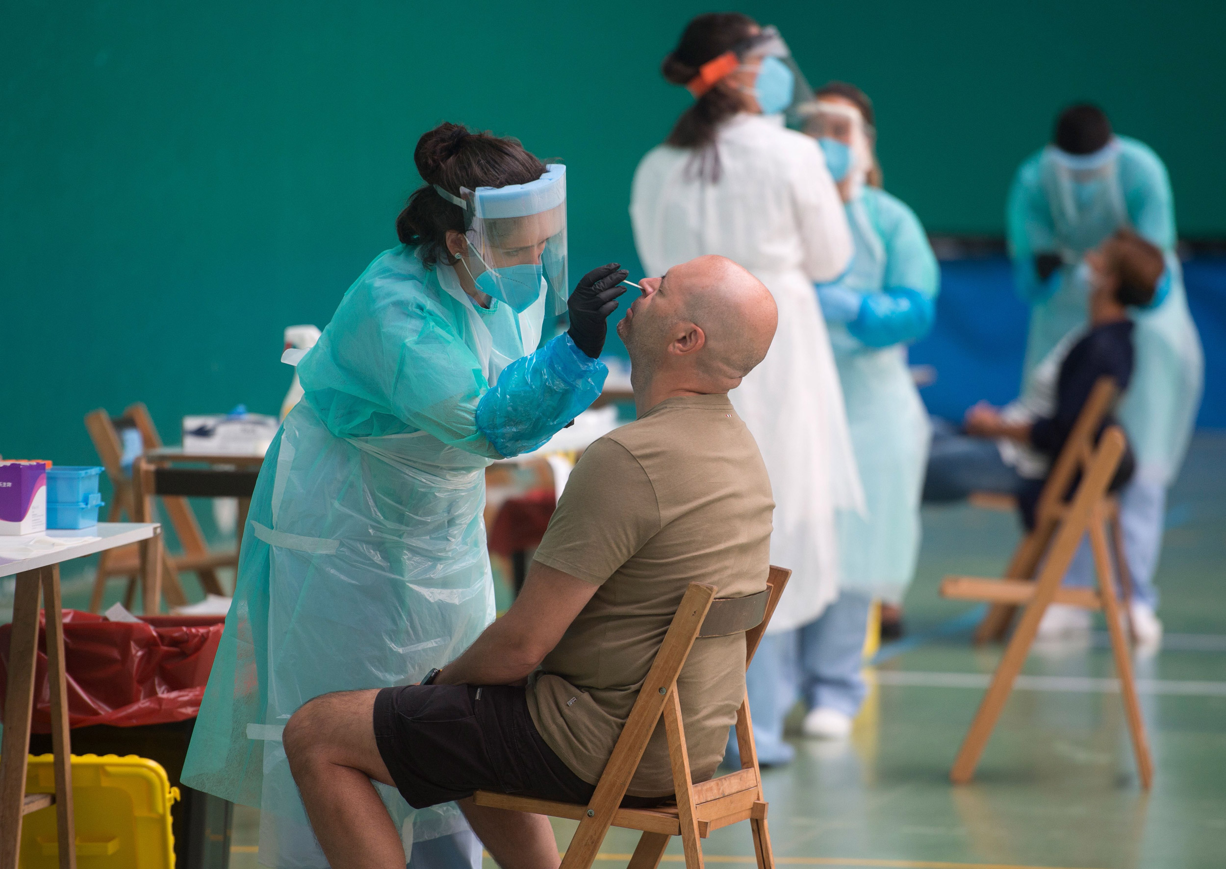 A healthcare worker uses a swab to collect a sample at a temporary testing center for coronavirus in the Spanish Basque city of Getaria on July 15.