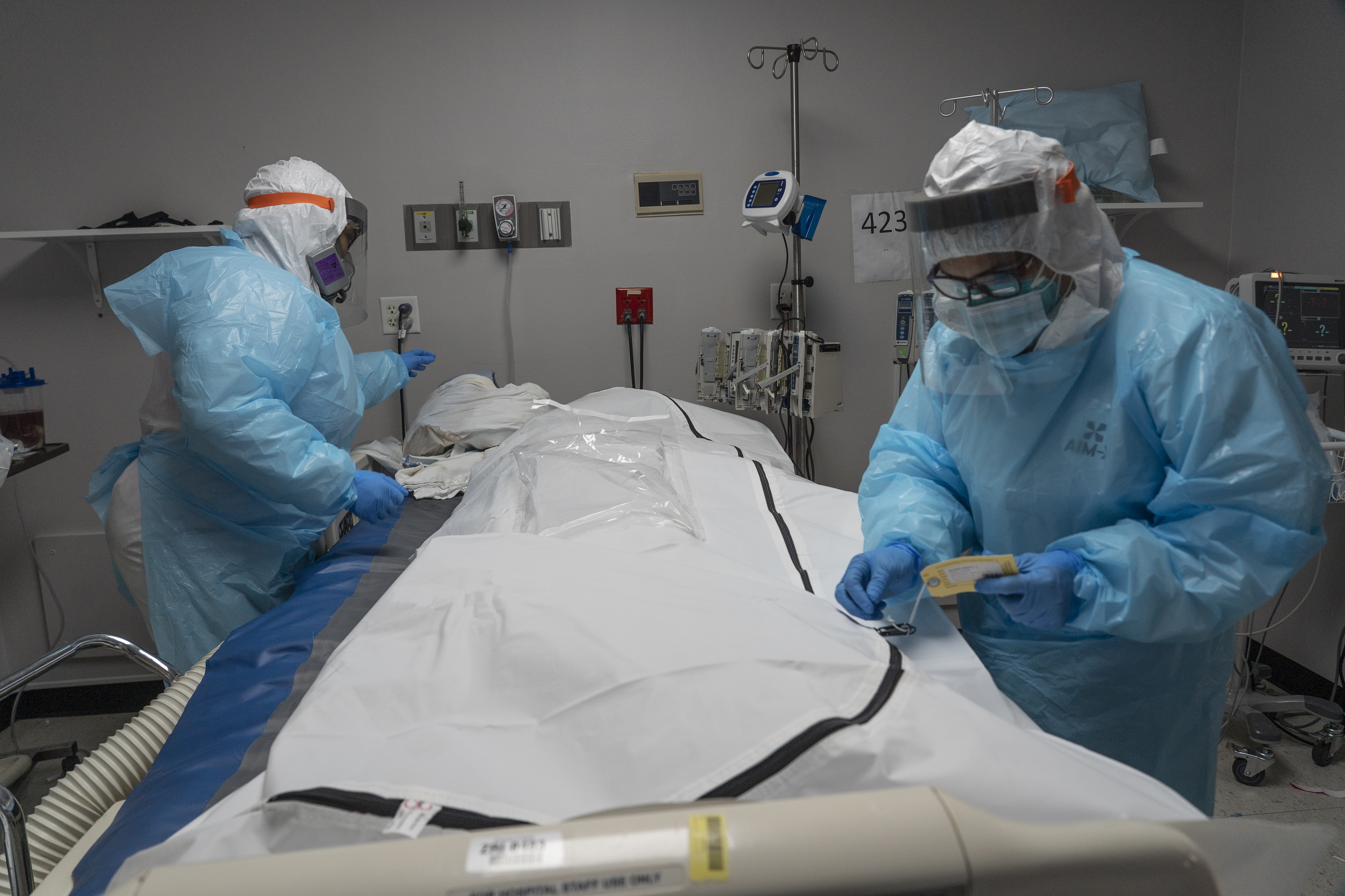 Medical staff members tends to a deceased COVID-19 patient's body in the coronavirus intensive care unit at the United Memorial Medical Center in Houston, Texas, on November 25.
