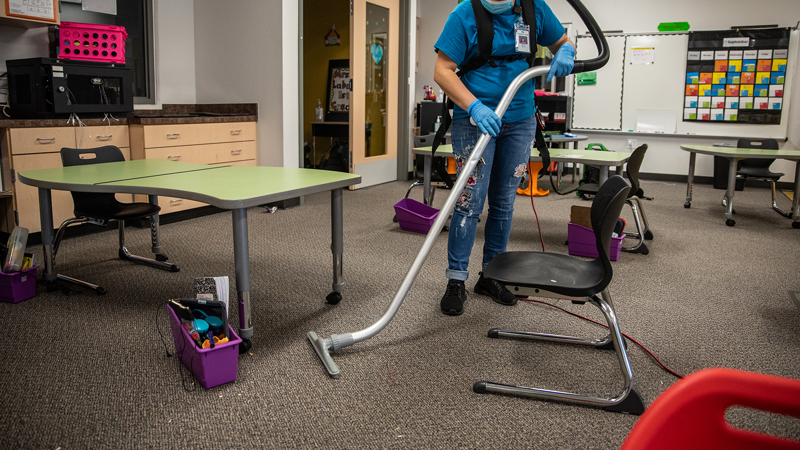 A custodial worker vacuums a classroom at an elementary school in Leander, Texas, on Friday, September 18, 2020.