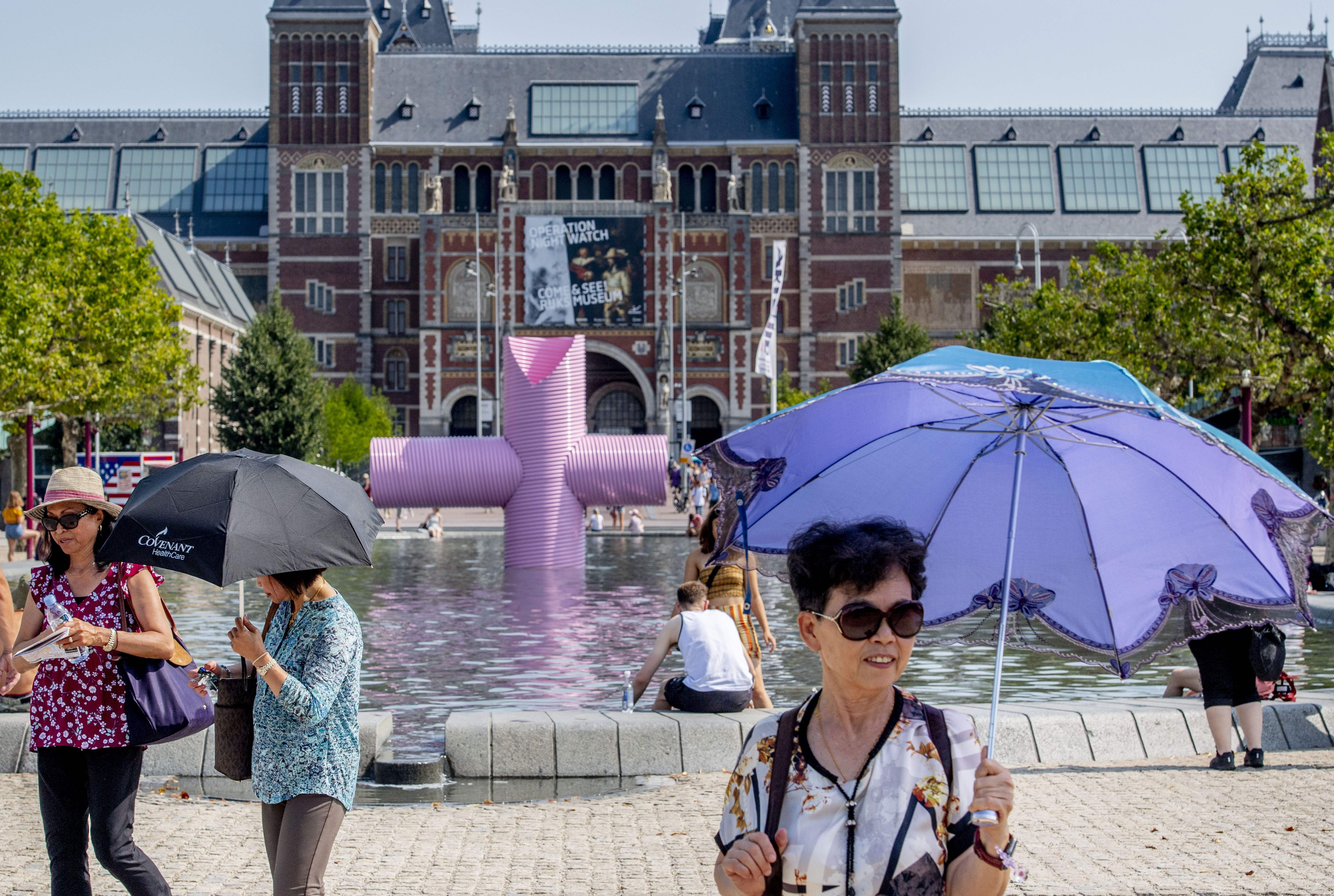 A woman holds an umbrella to protect herself from the sun as she walks past the Rijksmuseum in Amsterdam on Thursday.