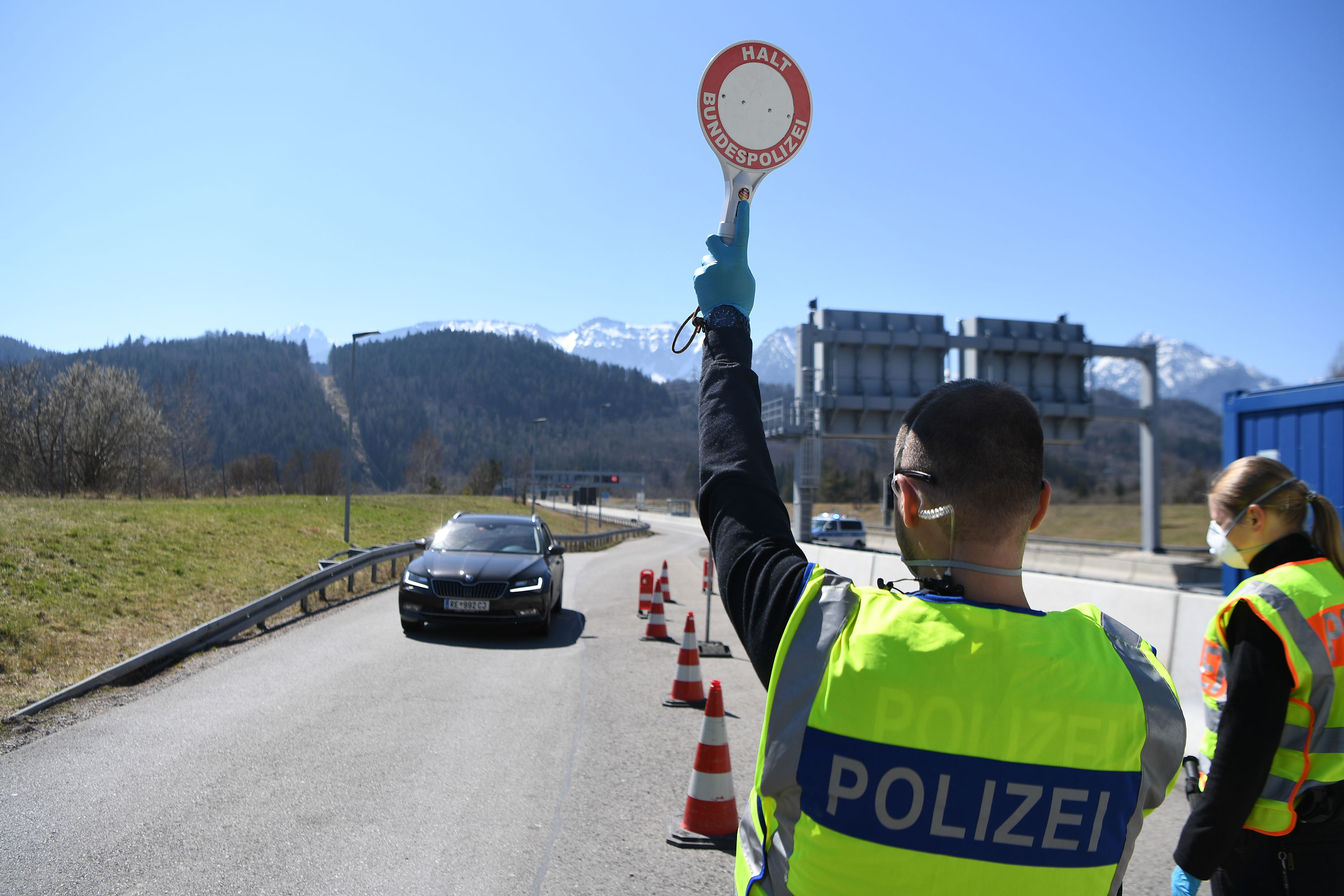 A German police officer stops a car at a checkpoint at the border to Austria near Fussen, Germany, on April 5.