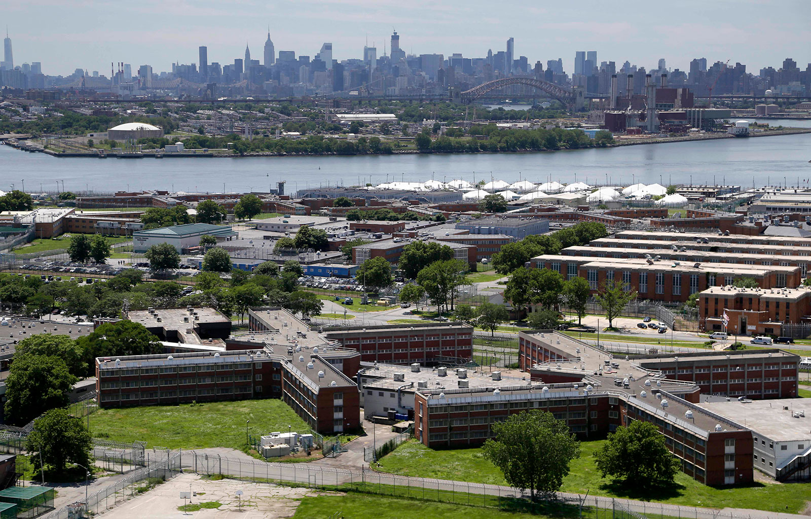 In a June 20, 2014 file photo, the Rikers Island jail complex stands in New York with the Manhattan skyline in the background.