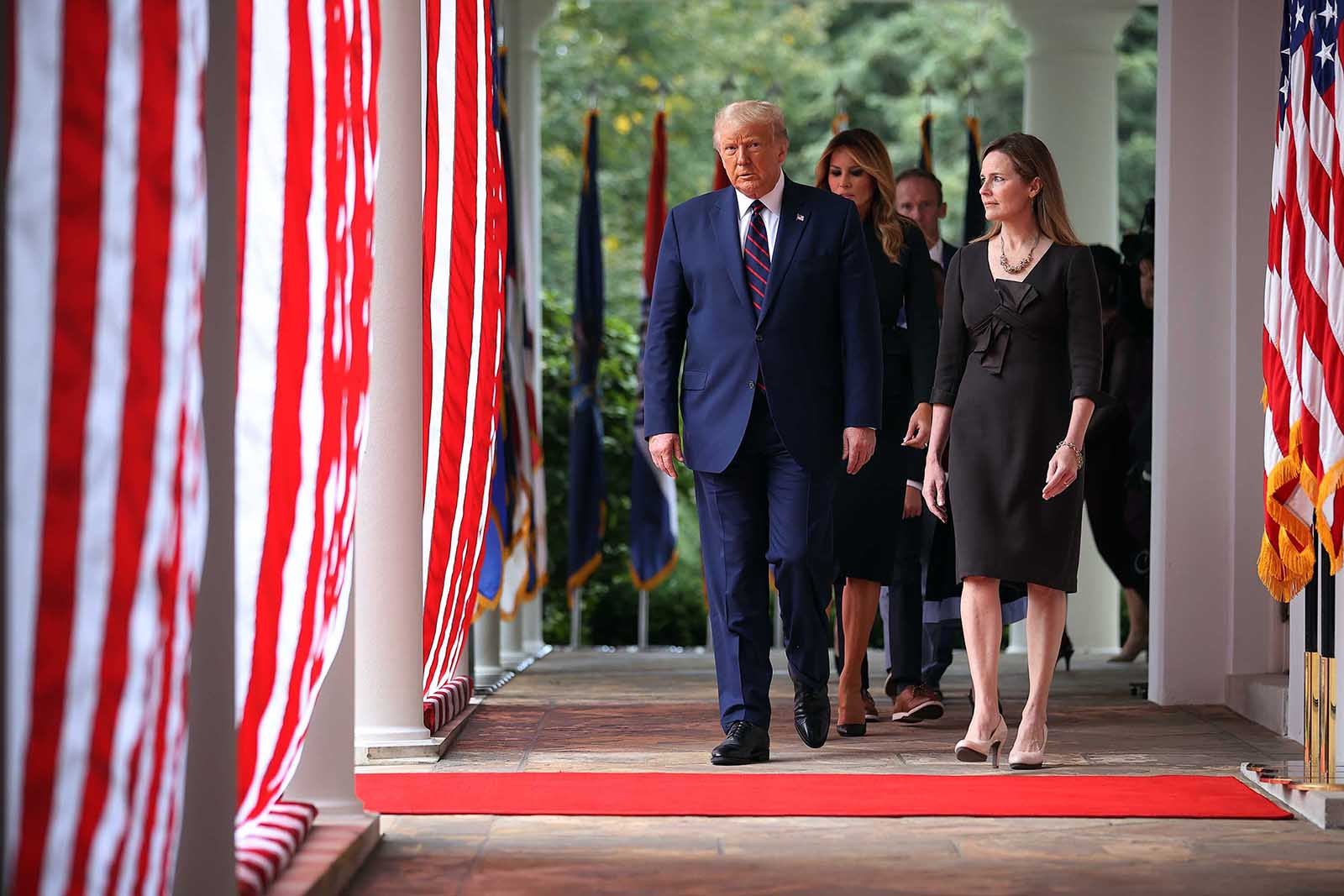 US President Donald Trump, first lady Melania Trump and 7th U.S. Circuit Court Judge Amy Coney Barrett, walk into the Rose Garden before Trump announces Barrett as his nominee to the Supreme Court at the White House September 26, in Washington.