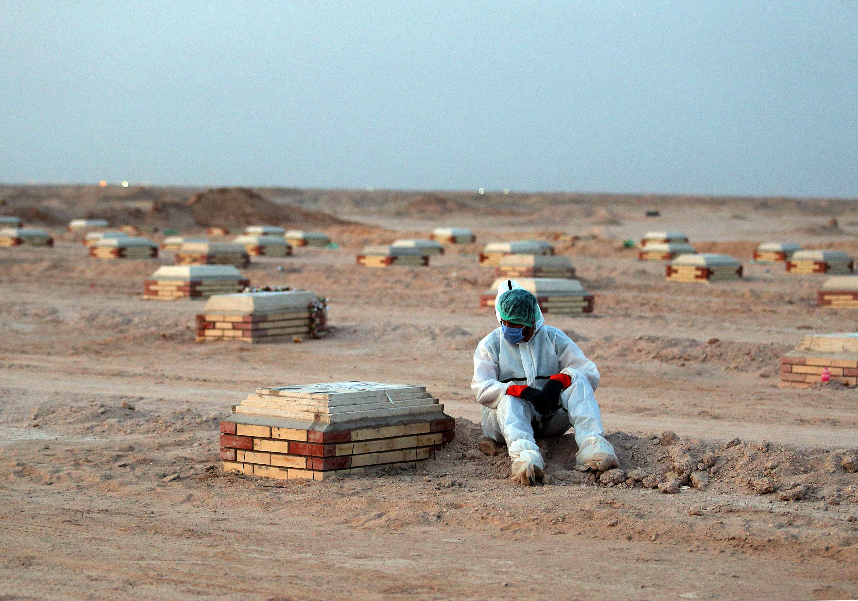 A person sits by a tombstone at a cemetery for Covid-19 victims near the city of Najaf in Iraq on June 10.
