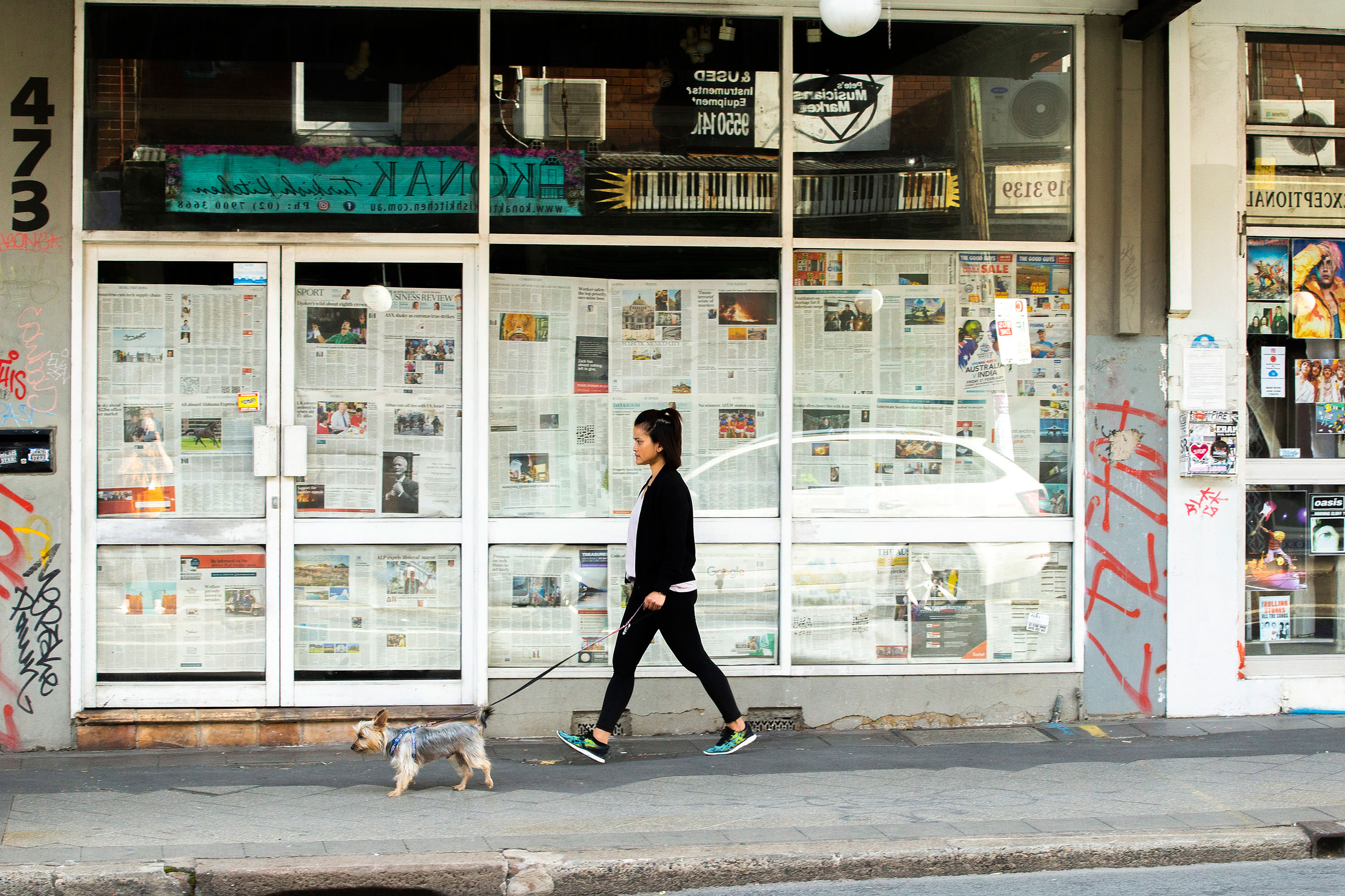 A woman walks past a closed shopfront on May 7 in Sydney, Australia.