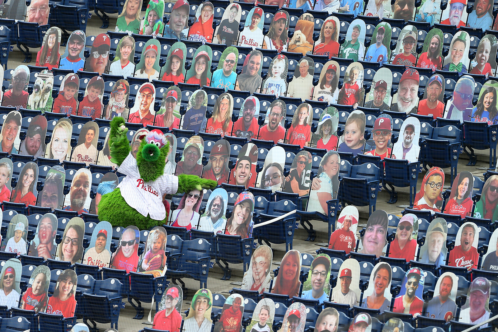 The Phillie Phanatic shows off the foul ball he caught amongst the cardboard cutout fans during an MLB baseball game between the Philadelphia Phillies and New York Mets at Citizens Bank Park on August 16, in Philadelphia, Pennsylvania.