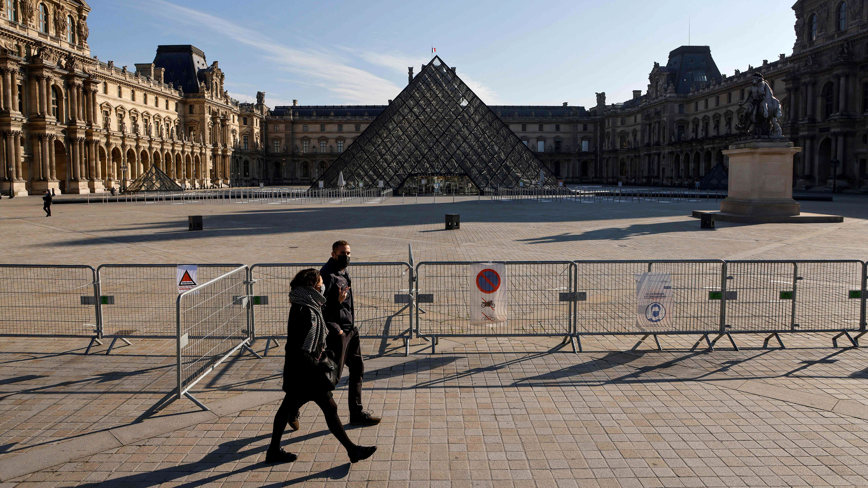 A couple walk by The Louvre Museum during a government-imposed lockdown on November 6 in Paris .