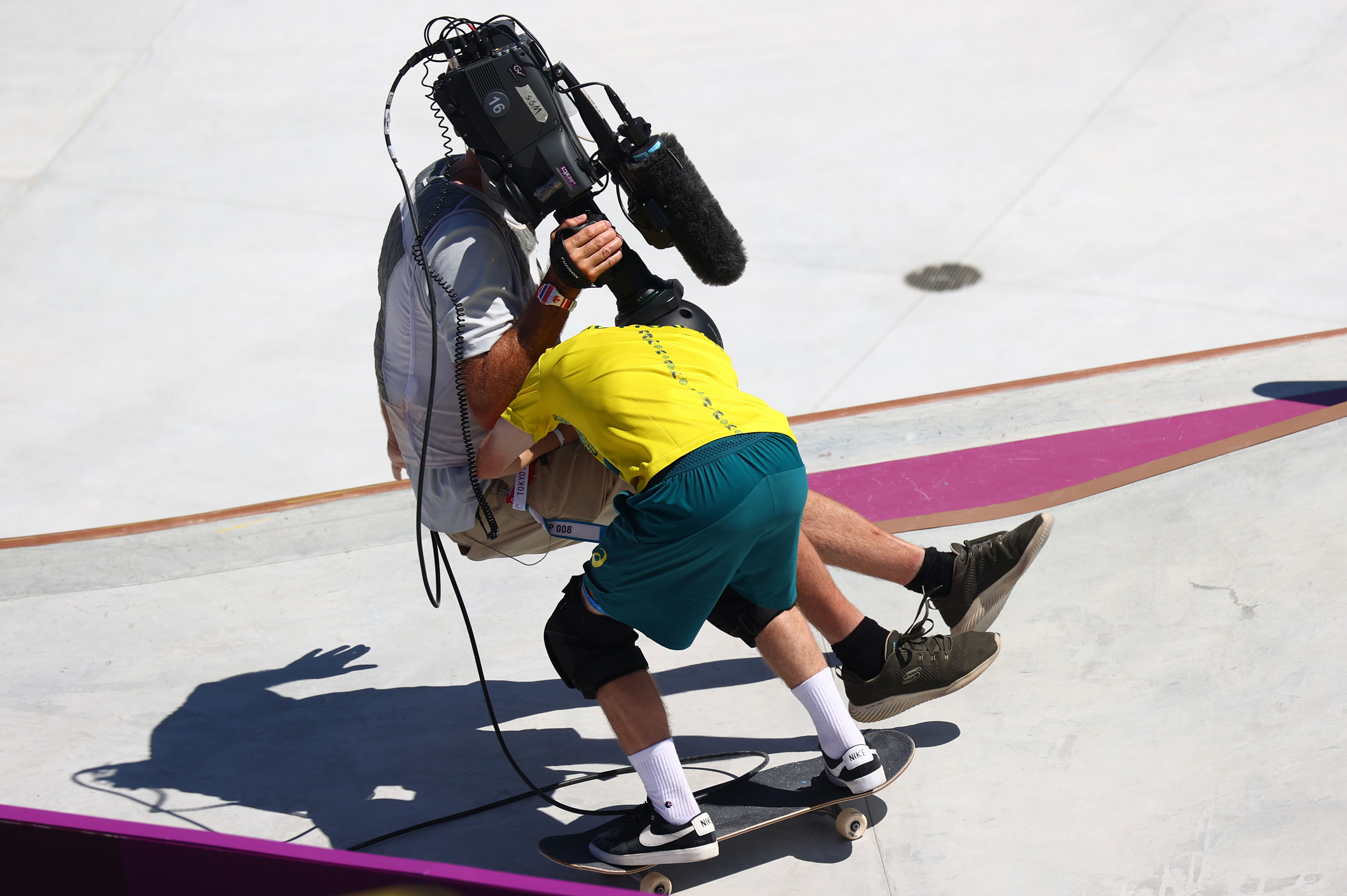 Kieran Woolley of Australia crashes into a cameraman during a park skateboarding preliminary round on August 5.