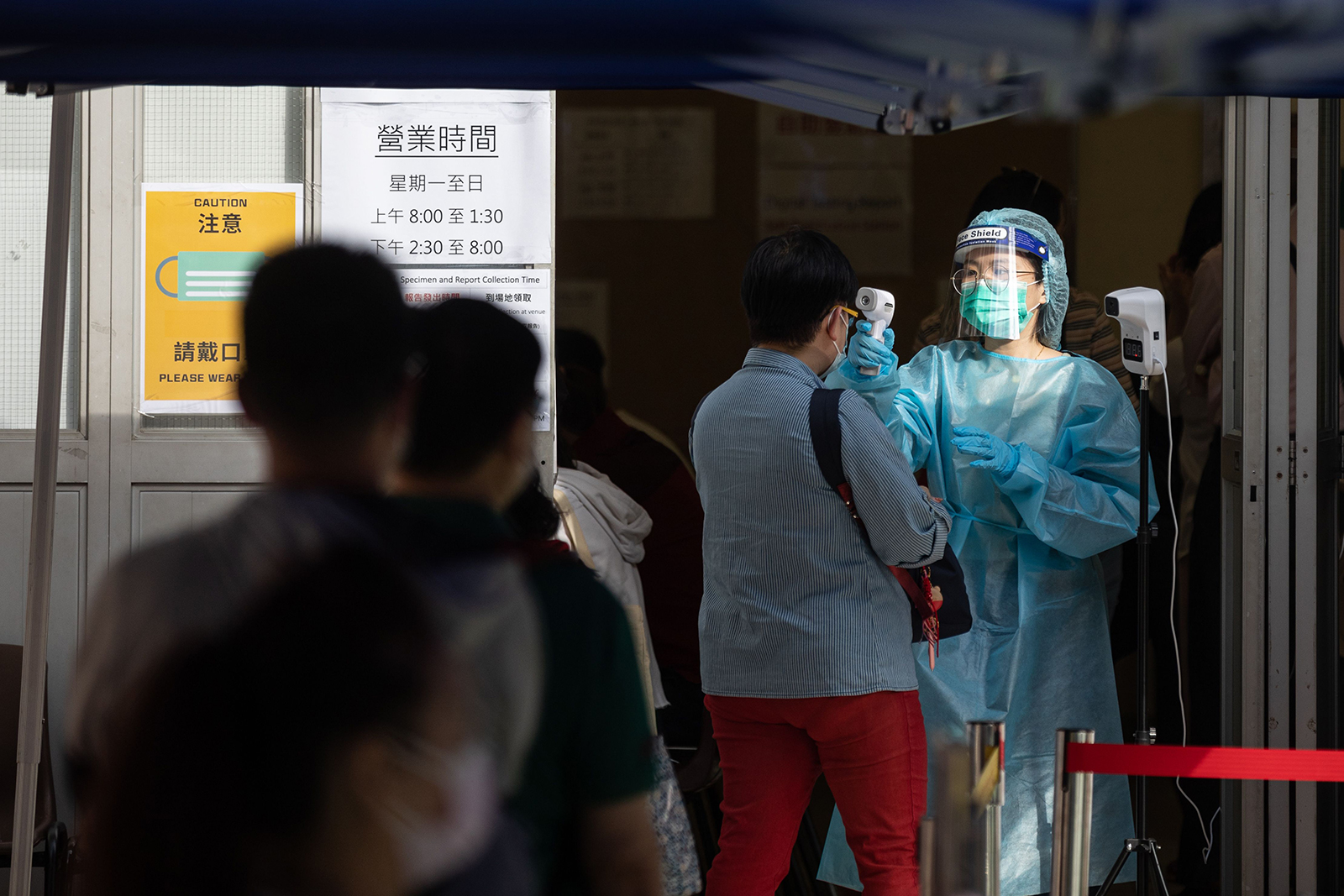 A health worker in protective gown checks the temperatures of visitors entering a community testing center in Hong Kong, on November 21.