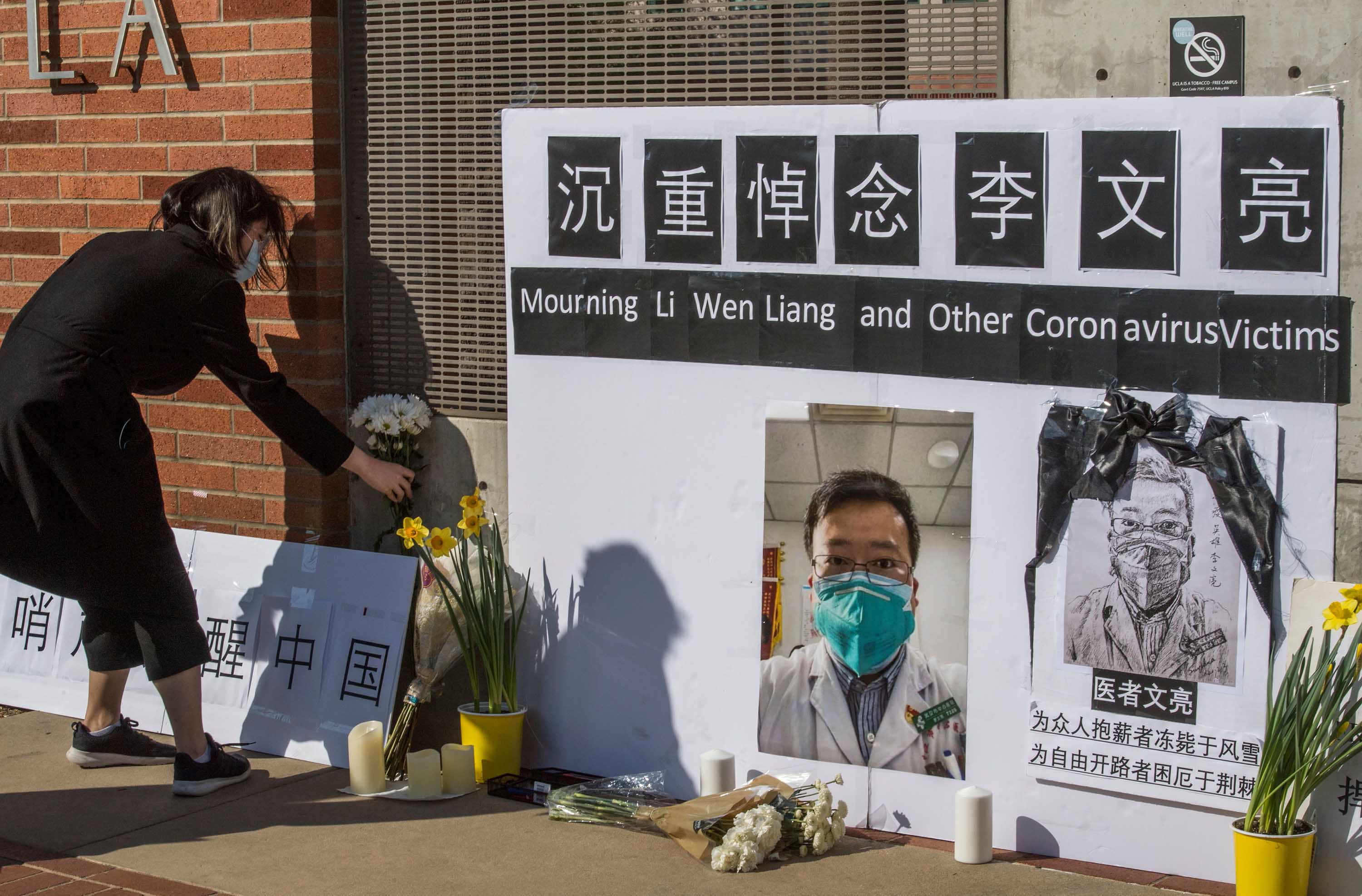 A woman leaves a flower tribute for Dr. Li Wenliang outside the UCLA campus in Westwood, California, on February 15, following news of his death from coronavirus.