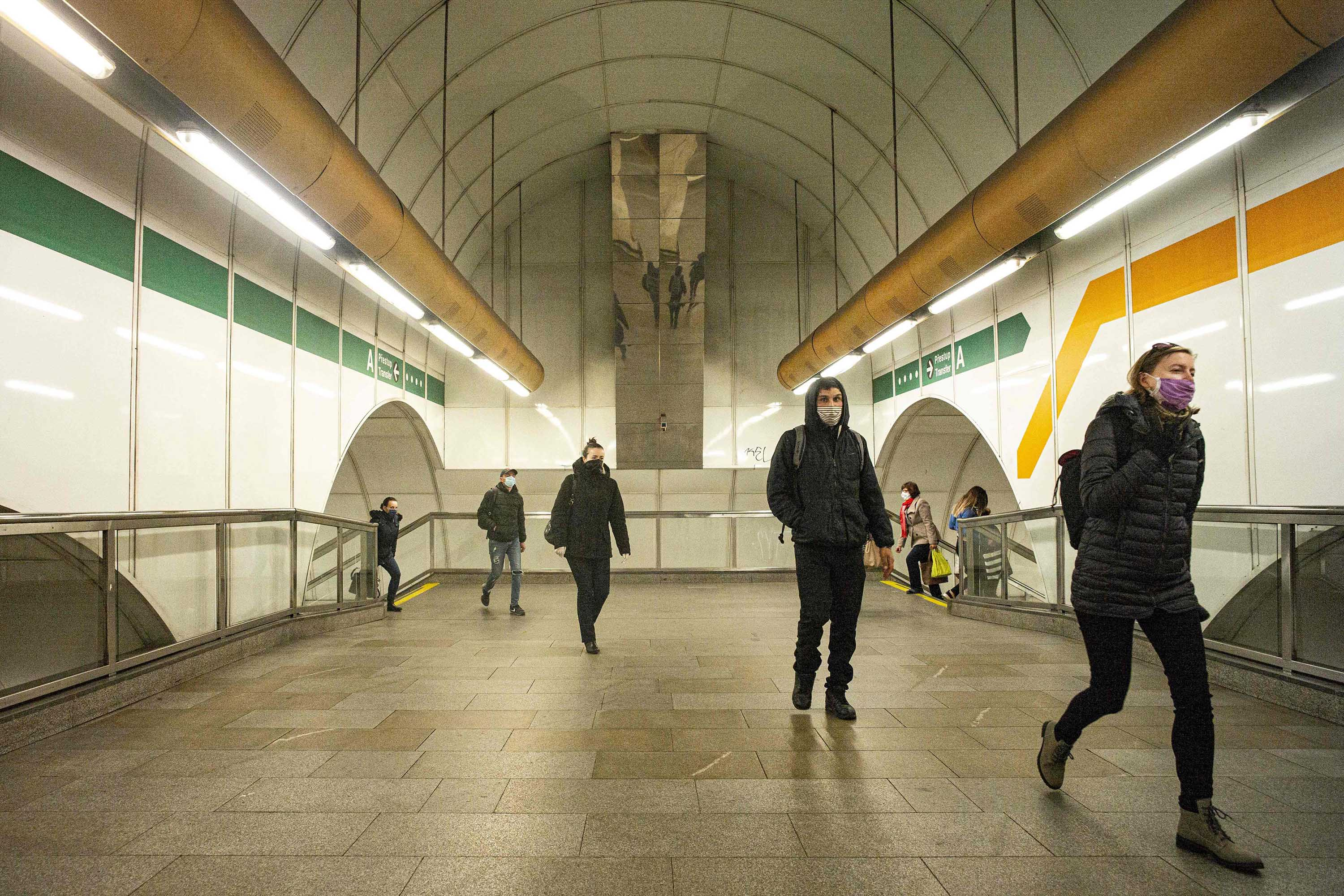 Commuters wearing face masks make their way through a metro station in Prague, the capital of the Czech Republic, on April 15.
