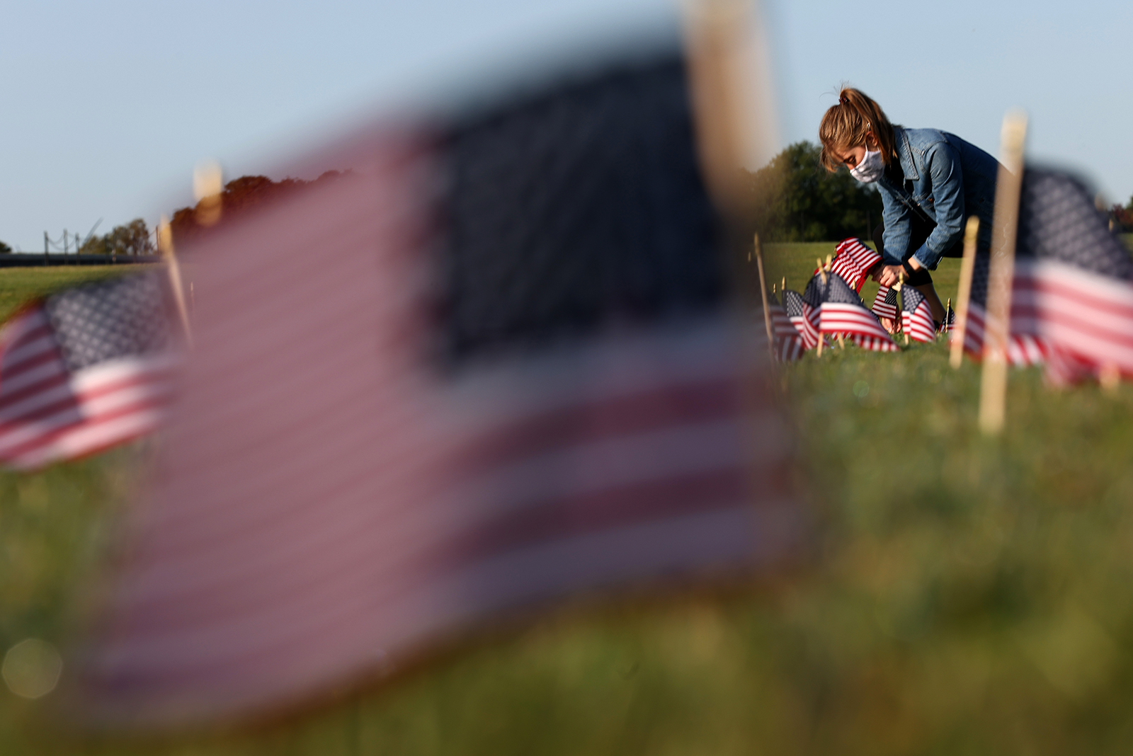 A woman places flags at a COVID Memorial Project installation of 20,000 American flags on the National Mall in Washington, DC, on September 22. The flags are displayed on the grounds of the Washington Monument facing the White House.