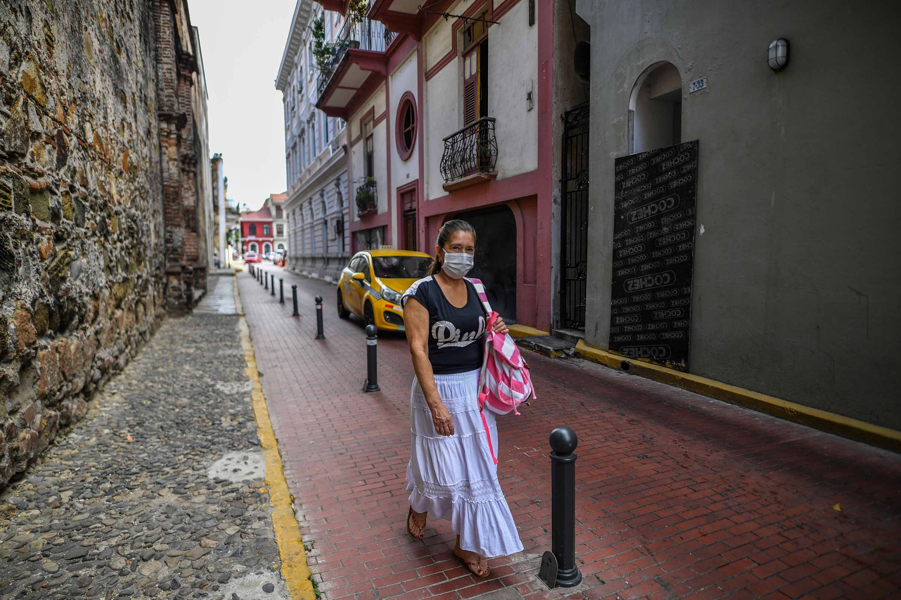 A woman wearing a face mask as a precautionary measure against the spread the coronavirus walks in downtown Panama City on March 17.