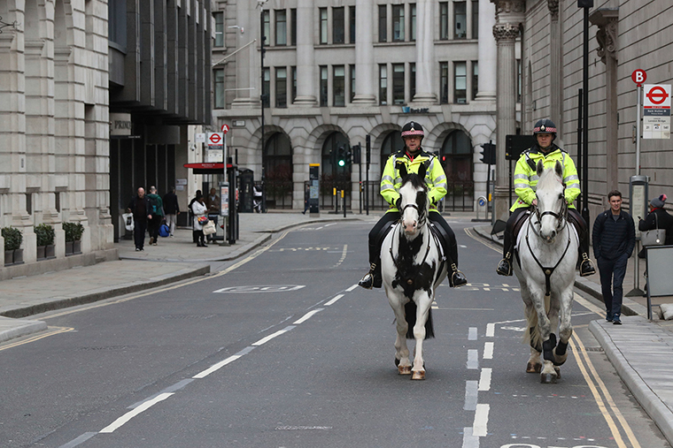 Mounted police patrol a quiet street in the City of London, adopting social distancing on horseback, as the UK's coronavirus epicentre is concentrated in London, Friday March 20.