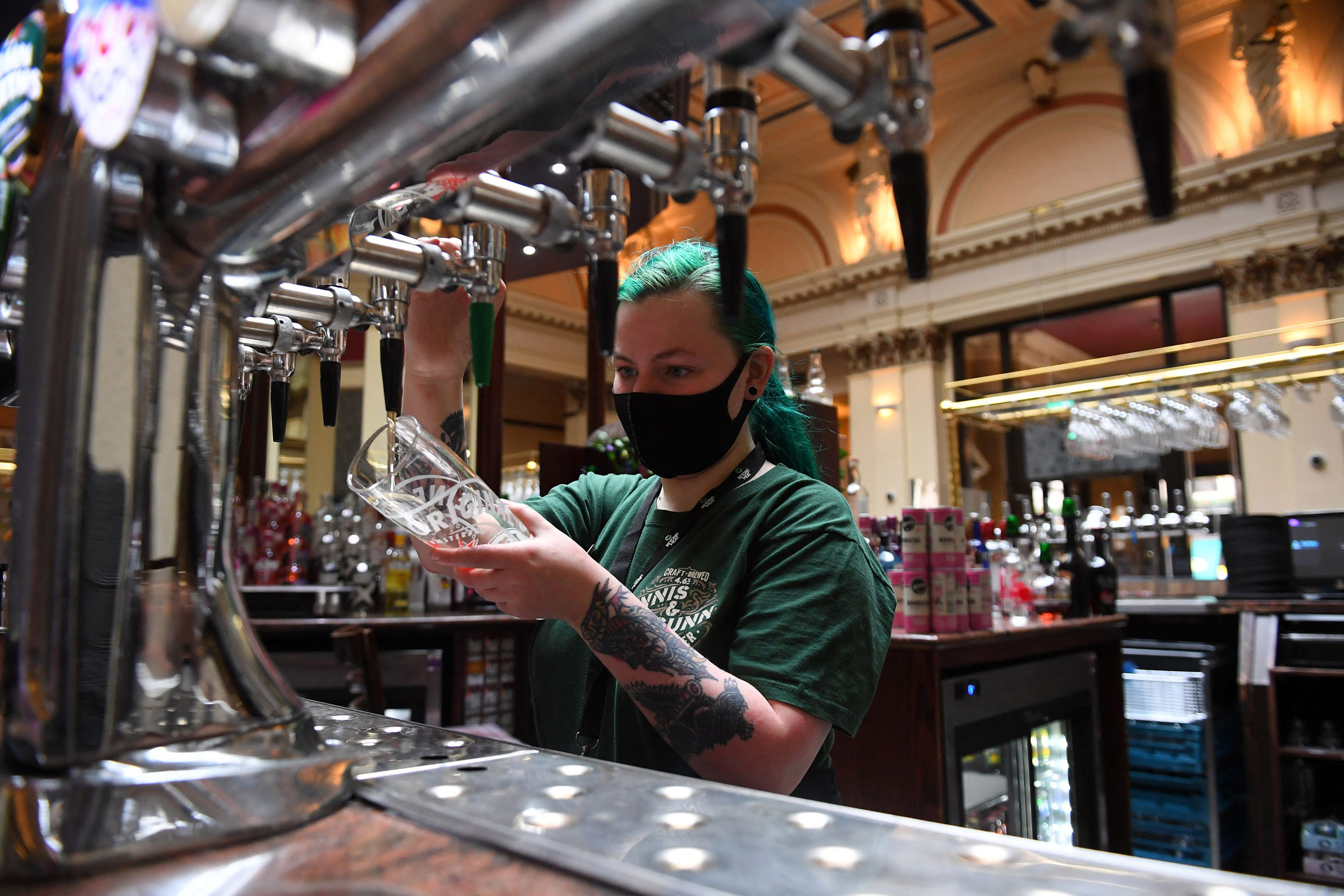 A bar worker prepares customers' drinks at a re-opened Wetherspoons pub in Glasgow on April 26, following the relaxing of some Covid-19 restrictions in Scotland.