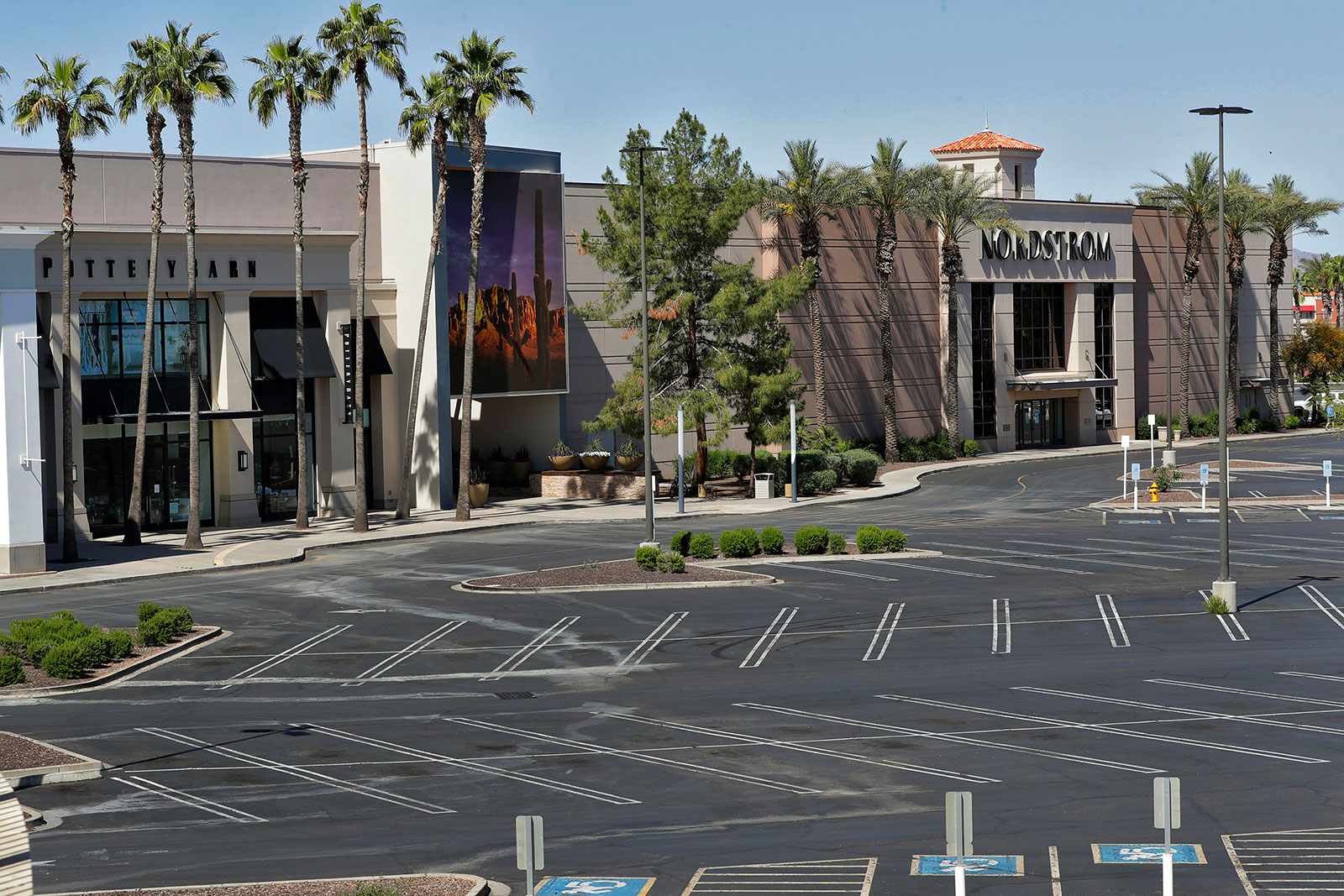 An empty parking lot at a shopping center in Chandler, Arizona, on April 4. Arizona will allow all retail stores to do in-person business again starting Friday.