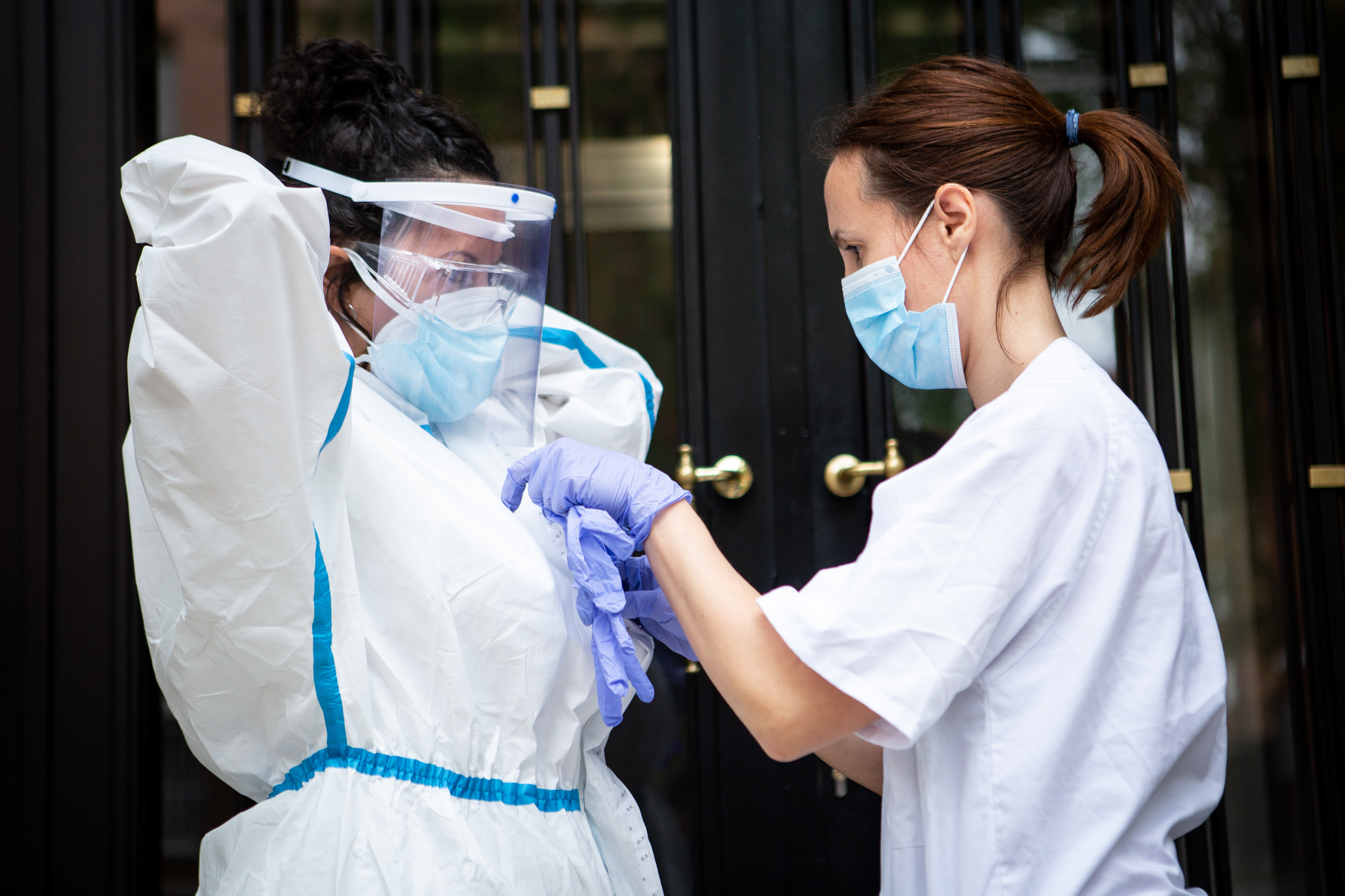 A nurse helps another nurse to put on a personal protective equipment before accessing a patient's home on April 17 in Madrid, Spain.