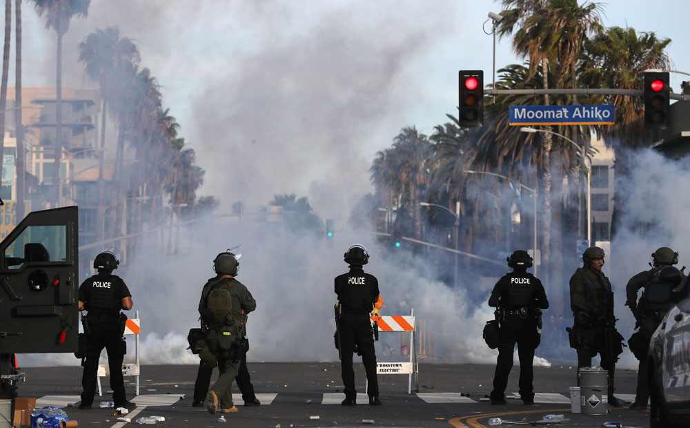 Police watch as tear gas is deployed during demonstrations in the aftermath of George Floyd's death on May 31, in Santa Monica, California.