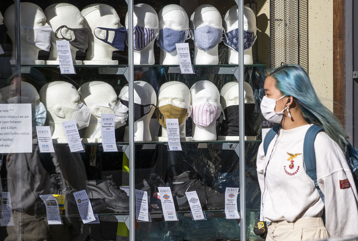 A woman walks past a shop selling masks in Edinburgh, Scotland on September 22.