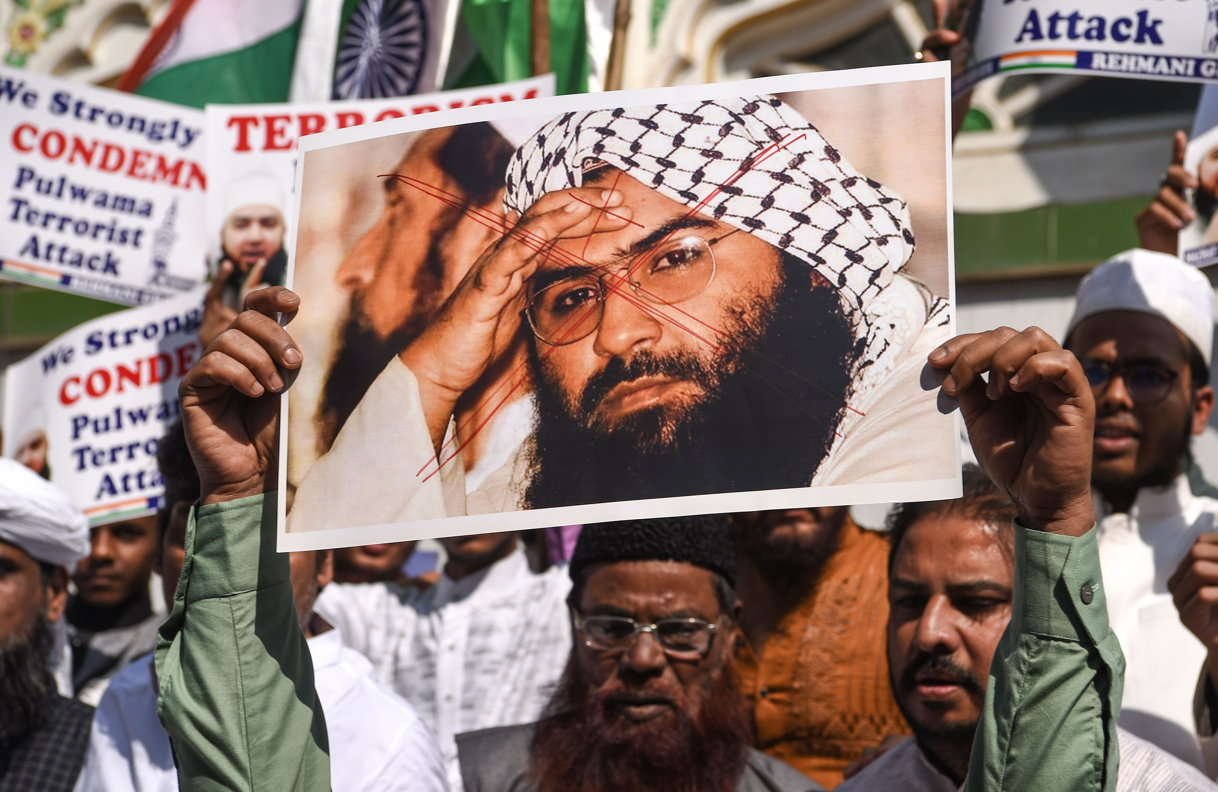 Indian Muslims hold a scratched photo of Jaish-e-Mohammad group chief, Maulana Masood Azhar, during a protest in Mumbai on February 15, 2019, the day after an attack on a paramilitary Central Reserve Police Force (CRPF) convoy in Kashmir.