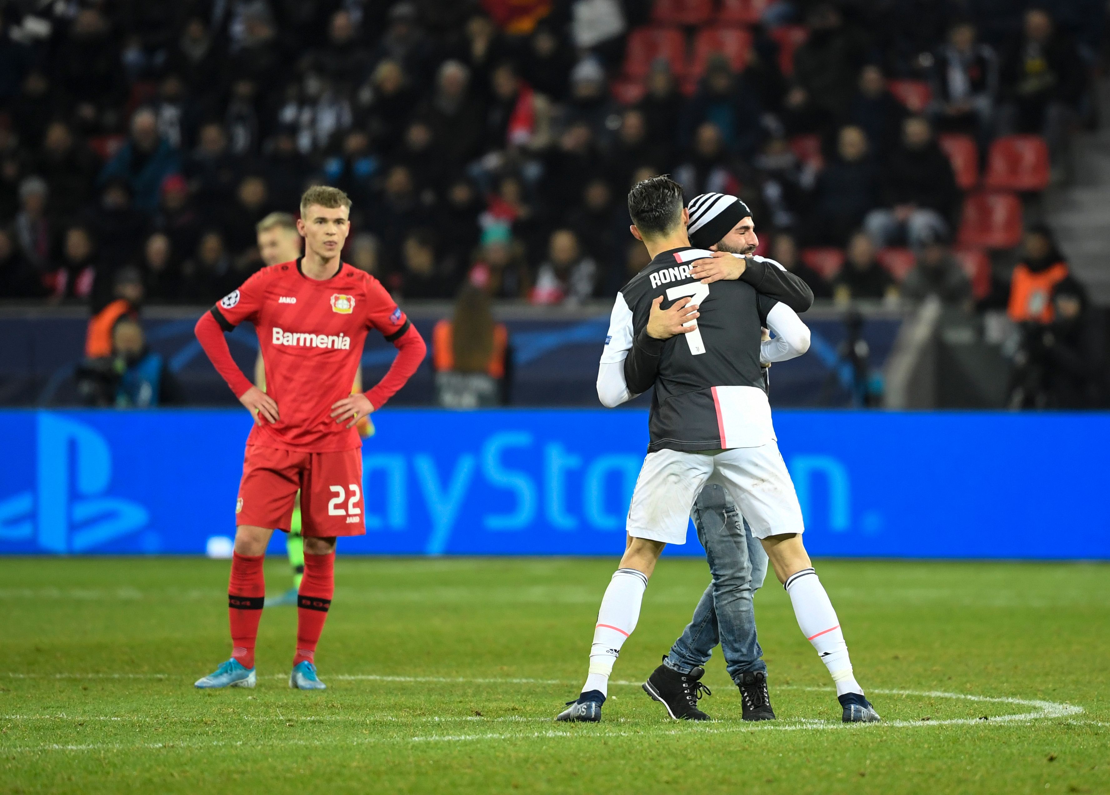 A pitch invader in Leverkusen enters the pitch to hug Cristiano Ronaldo.