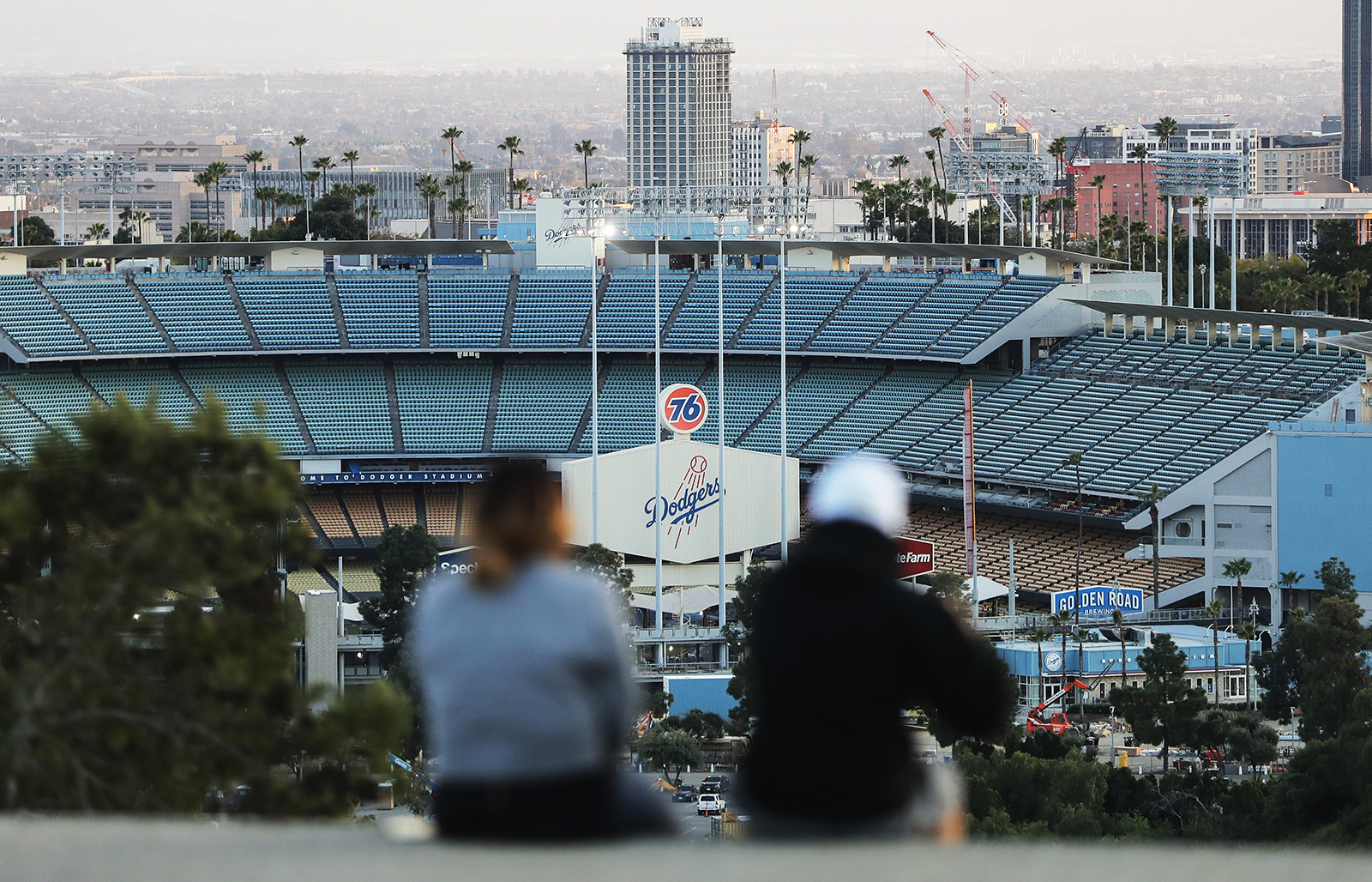 People sit on a hill overlooking Dodger Stadium in Los Angeles on what was supposed to be Major League Baseball's opening day, on March 26.