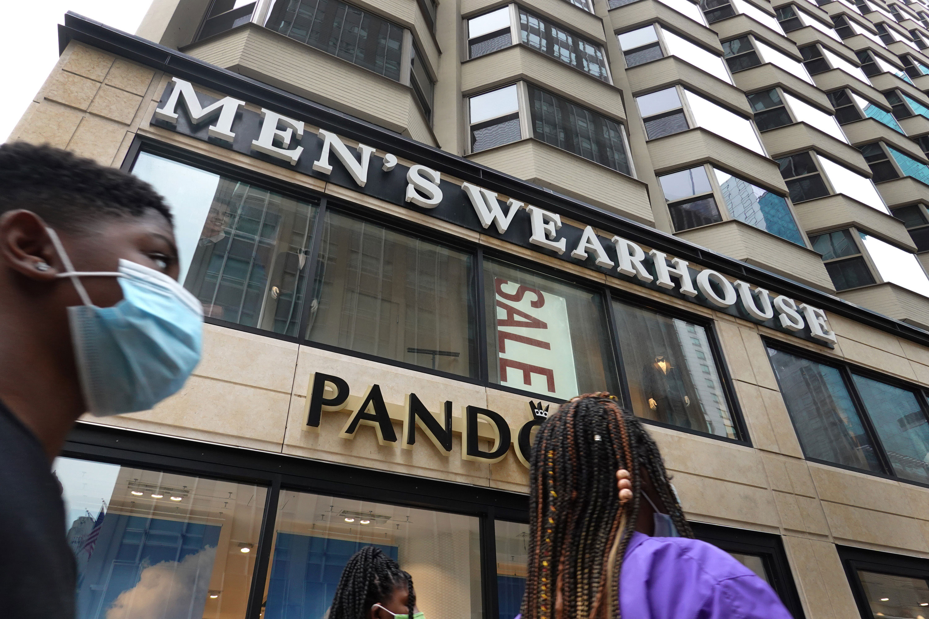 People walk past a Men's Wearhouse store on July 21 in Chicago, Illinois.
