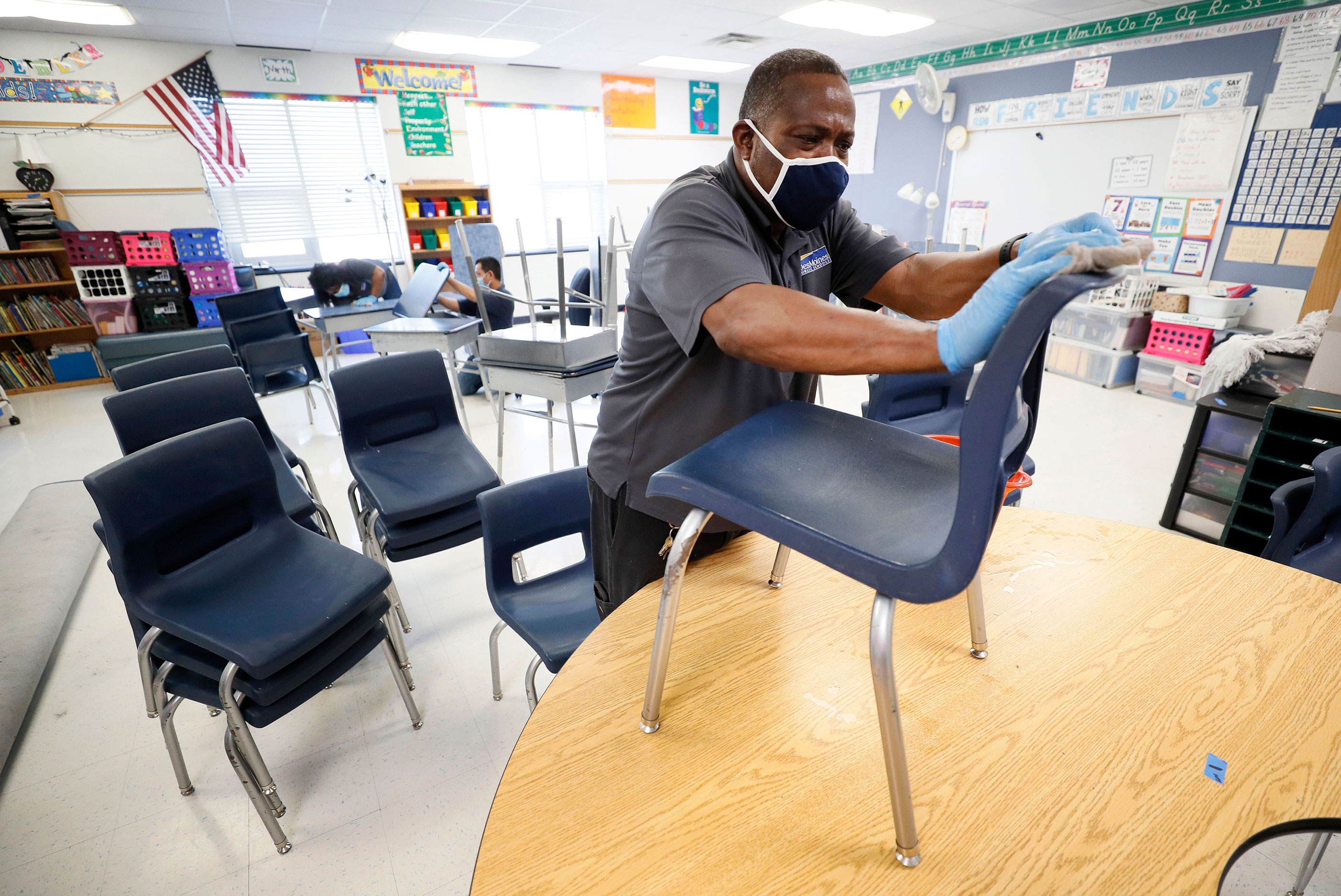 Custodian Tracy Harris cleans chairs in a classroom at Brubaker Elementary School on July 8 in Des Moines, Iowa.