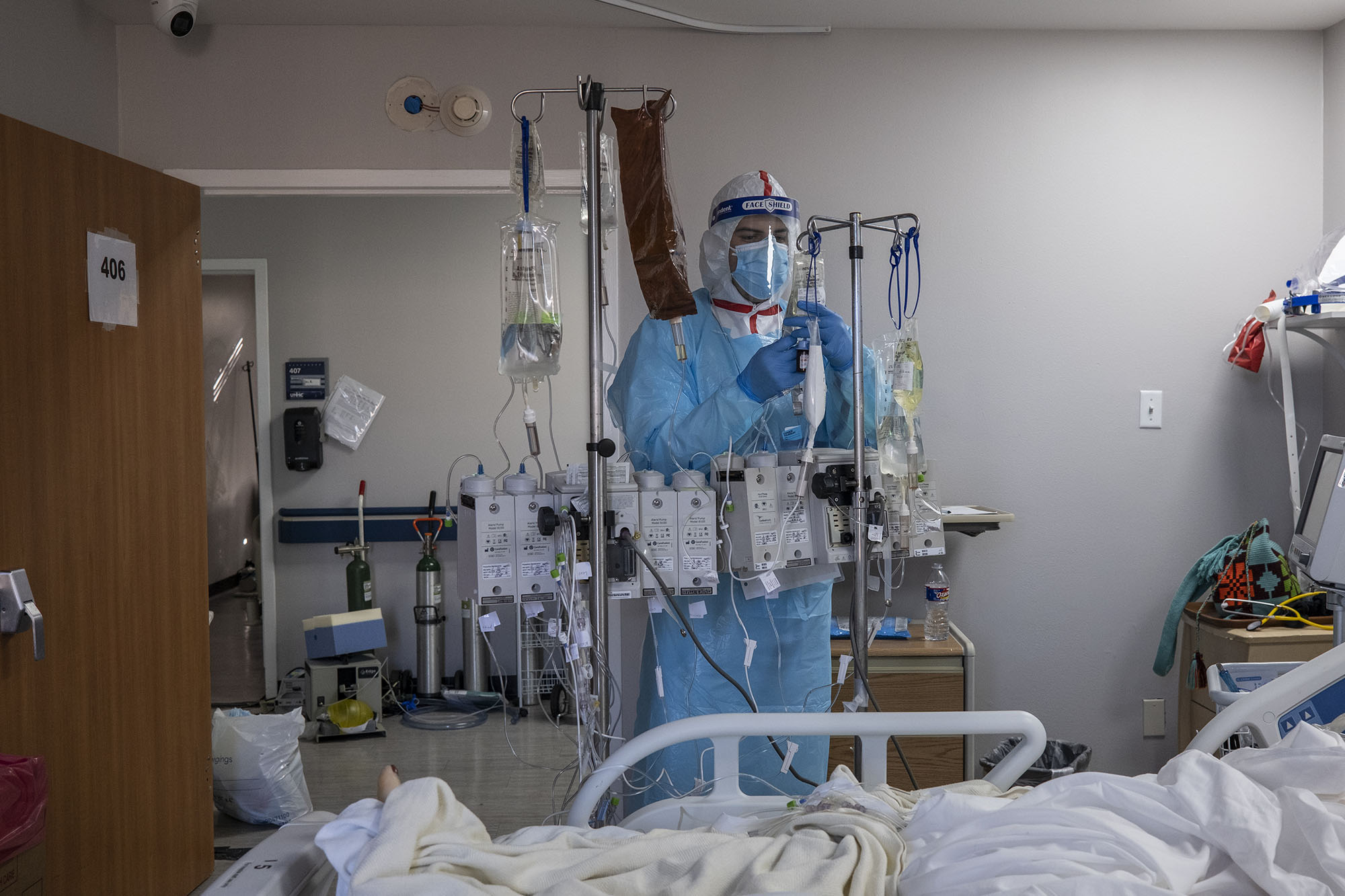 Medical staff member Alan Araiza checks of an IV for a patient in the Covid-19 intensive care unit at the United Memorial Medical Center on December 7 in Houston.