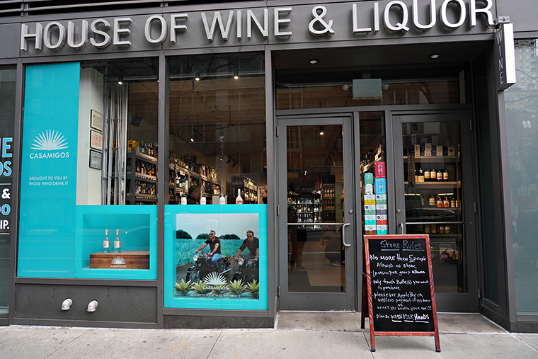 A sign listing the rules for entering the store is displayed in front of House of Wine & Liquor as the coronavirus continues to spread across the United States on March 16, 2020 in New York City.