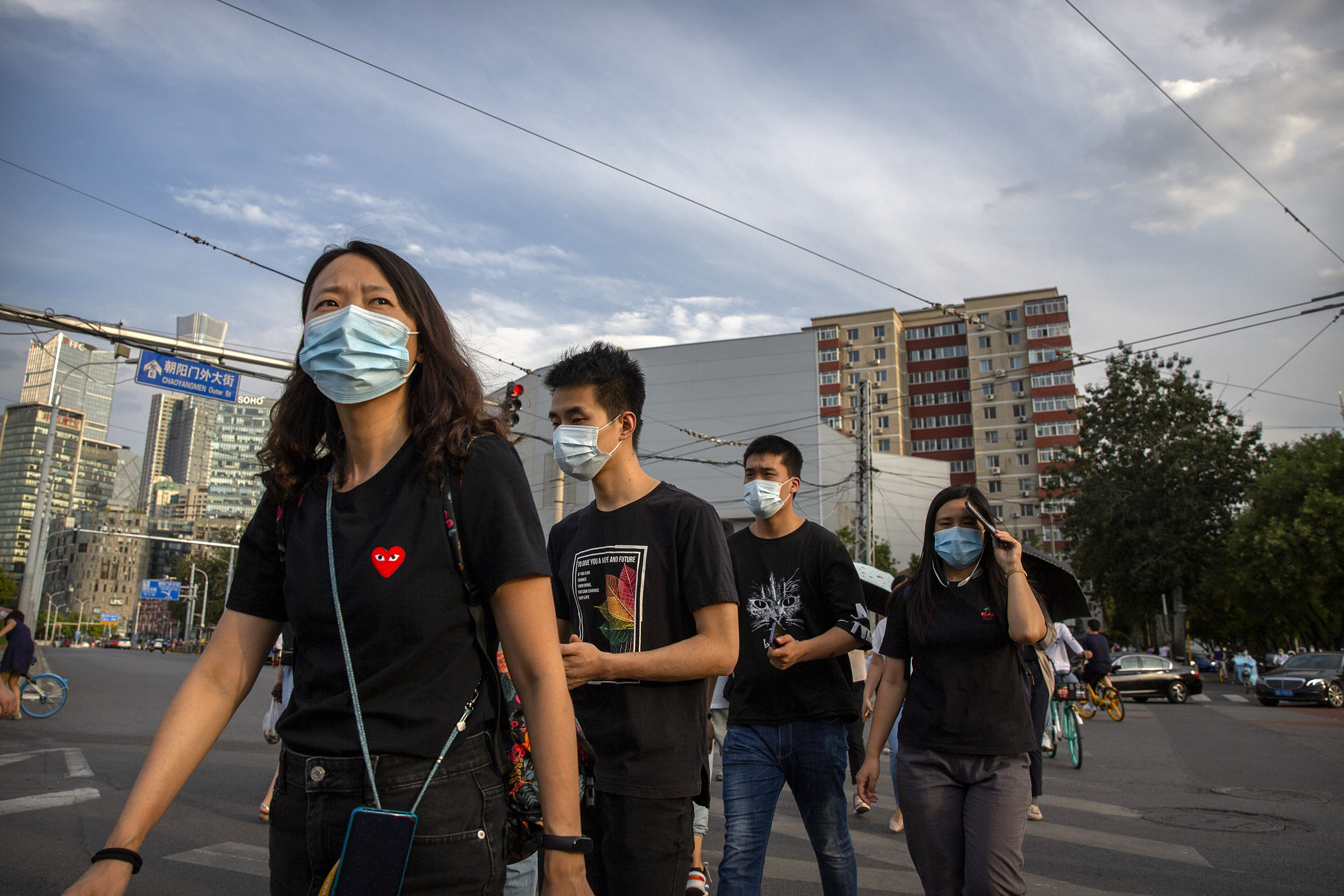 People wearing face masks to help protect against the spread of the coronavirus cross an intersection in Beijing, China, on Tuesday, August 4.