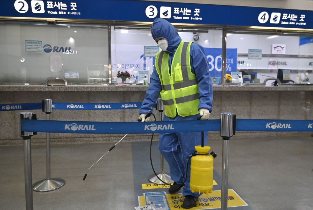A worker wearing protective gear sprays disinfectant at a railway station in Daegu, South Korea, on Wednesday.