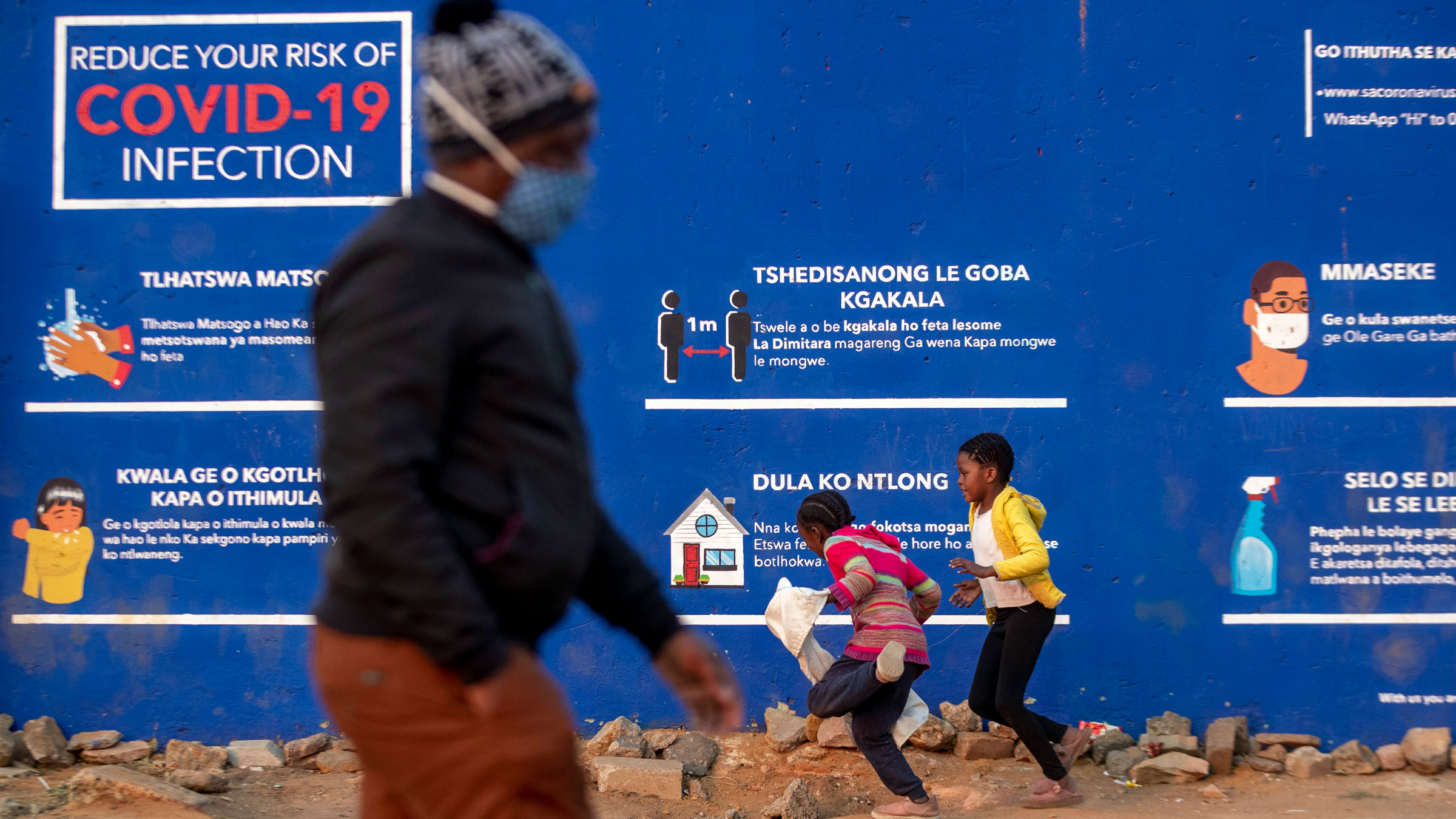 People walk past coronavirus guidance in Soweto, South Africa, on July 13.