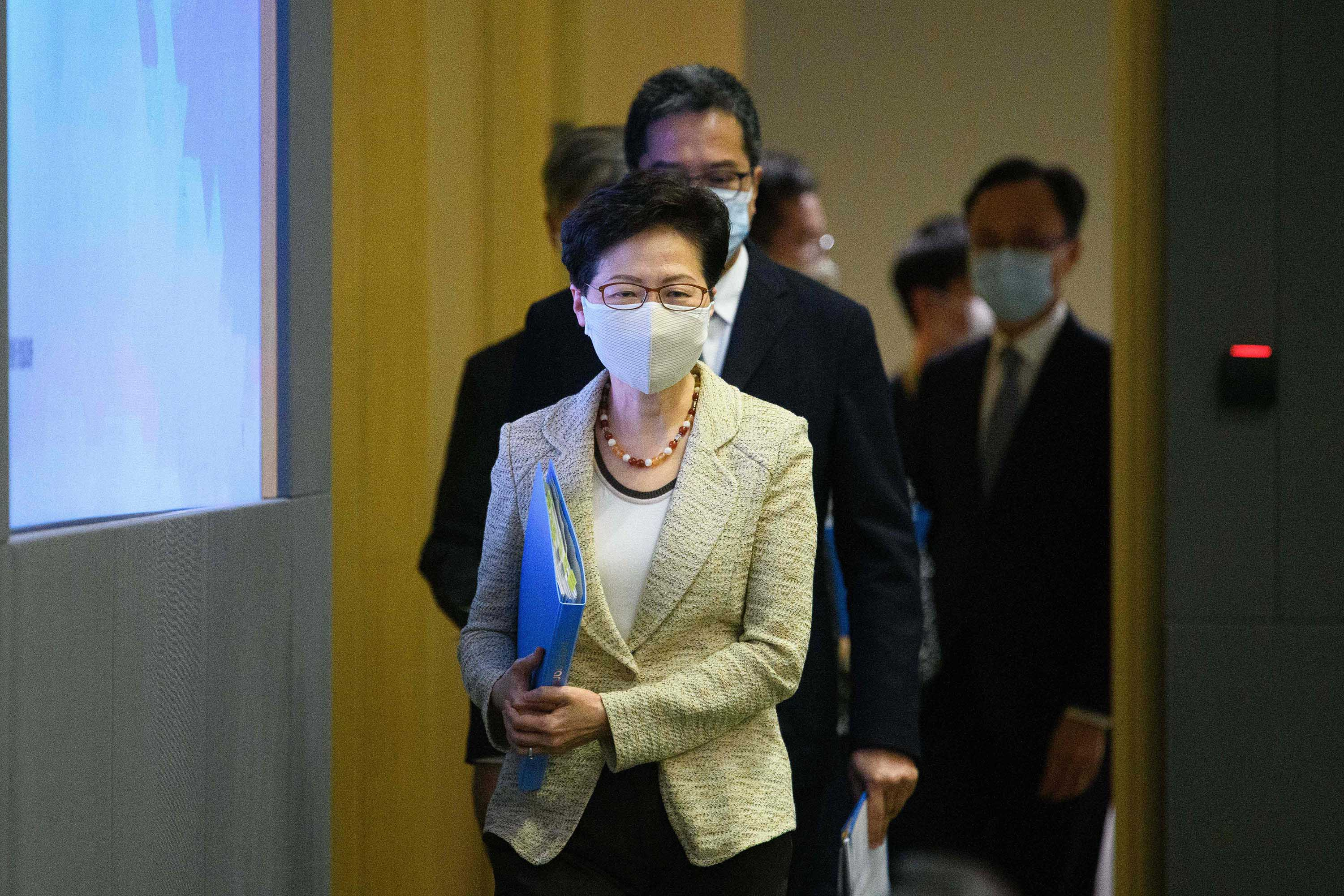 Hong Kong Chief Executive Carrie Lam and other government officials arrive for a press conference at government HQ on August 21, to provide details on the citywide testing initiative.