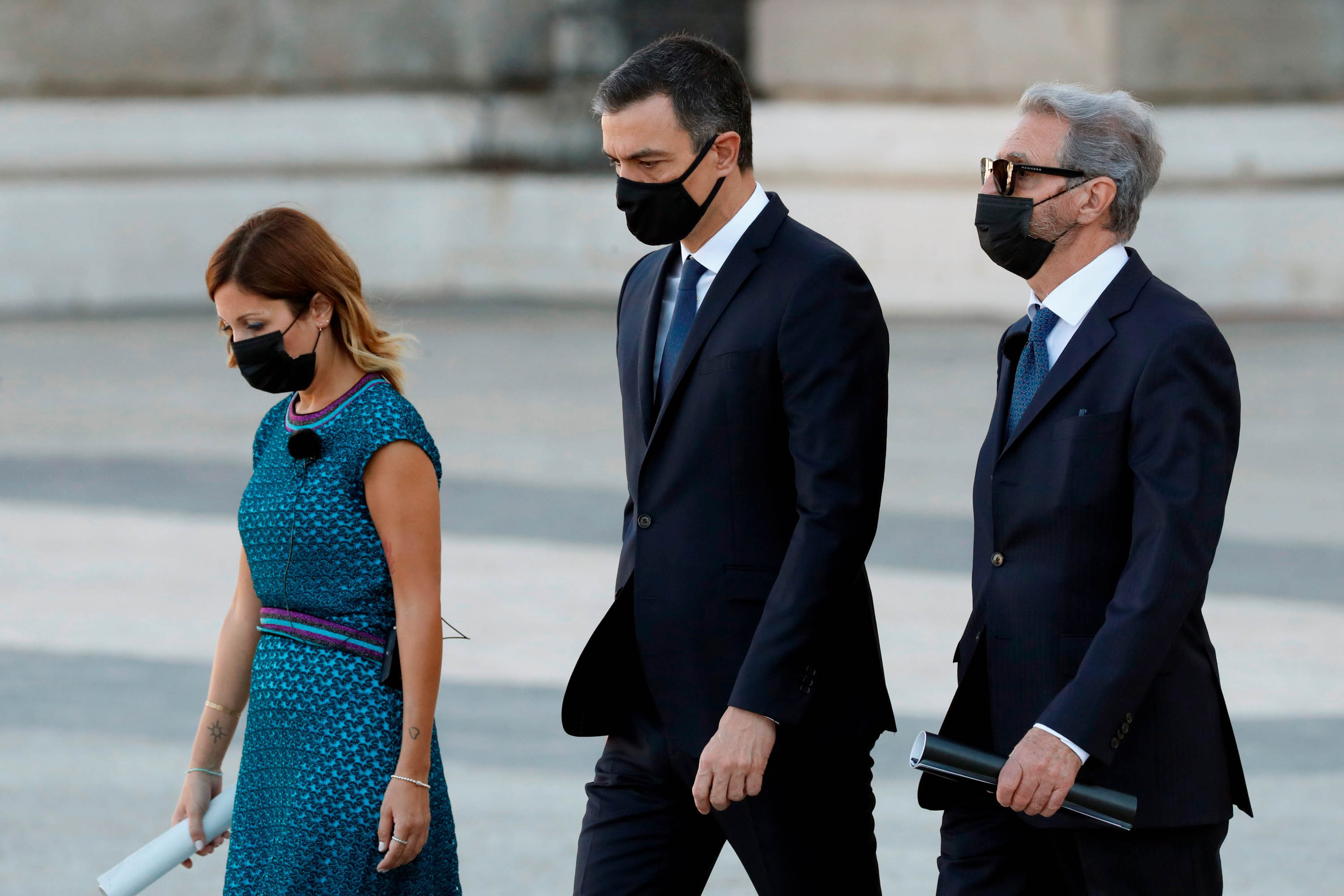 Spanish Prime Minister Pedro Sanchez, center, arrives at the ceremony in Madrid flanked by Catalan nurse Aroa Lopez, left, and Hernando Calleja, the brother of Spanish journalist José María Calleja, who died of Covid-19.