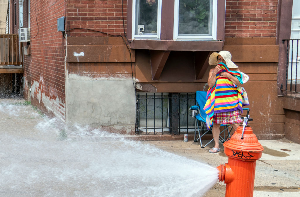 PA woman dries off after cooling down in the spray of a fire hydrant in 2018 in Philadelphia