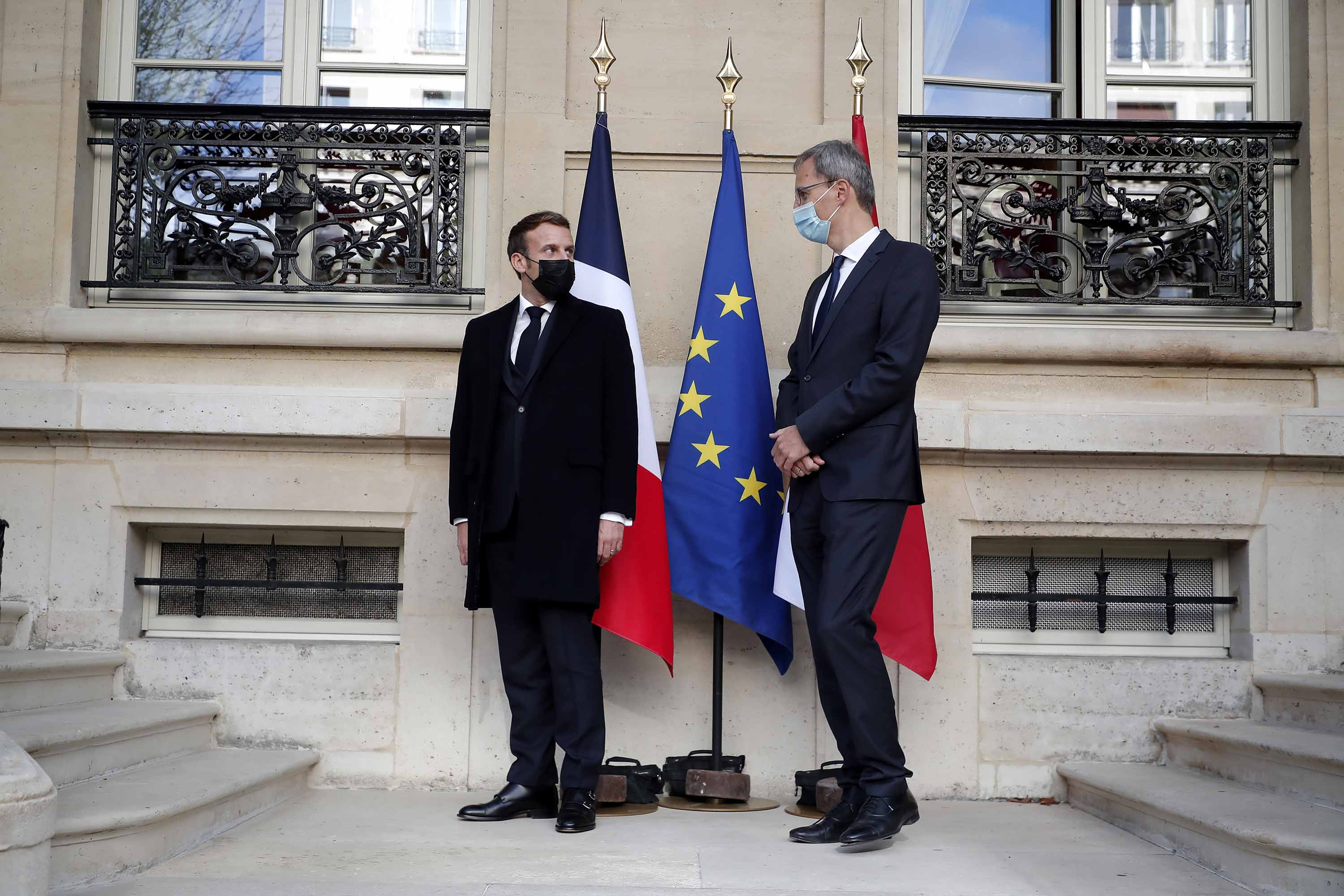 French President Emmanuel Macron, left, speaks with Wolfgang Wagner, Deputy Head of Mission at the Austrian embassy, before signing a condolence book for victims of the Vienna attack, in Paris, on Tuesday.