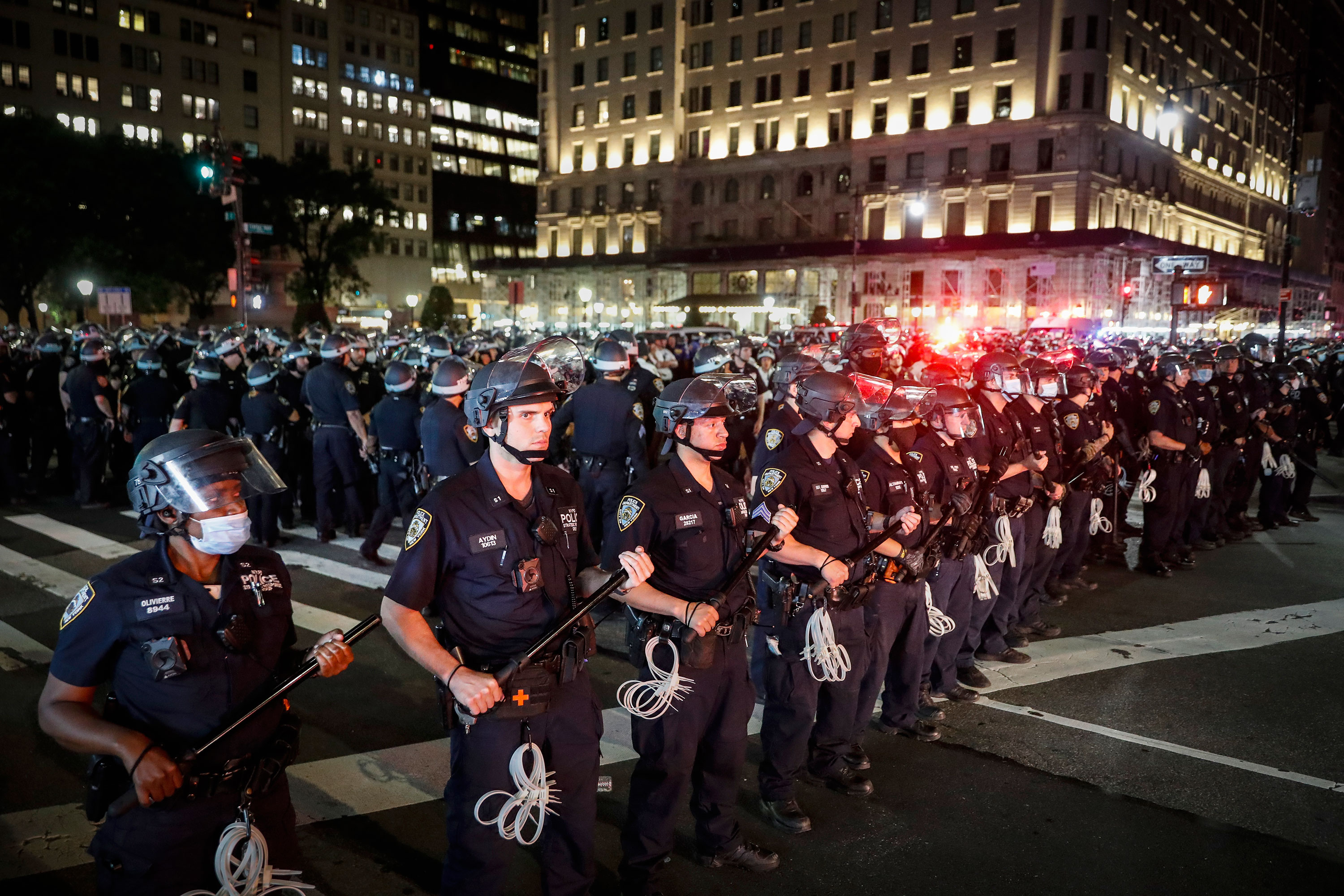 Police officers stand in formation after curfew on Thursday night in New York.