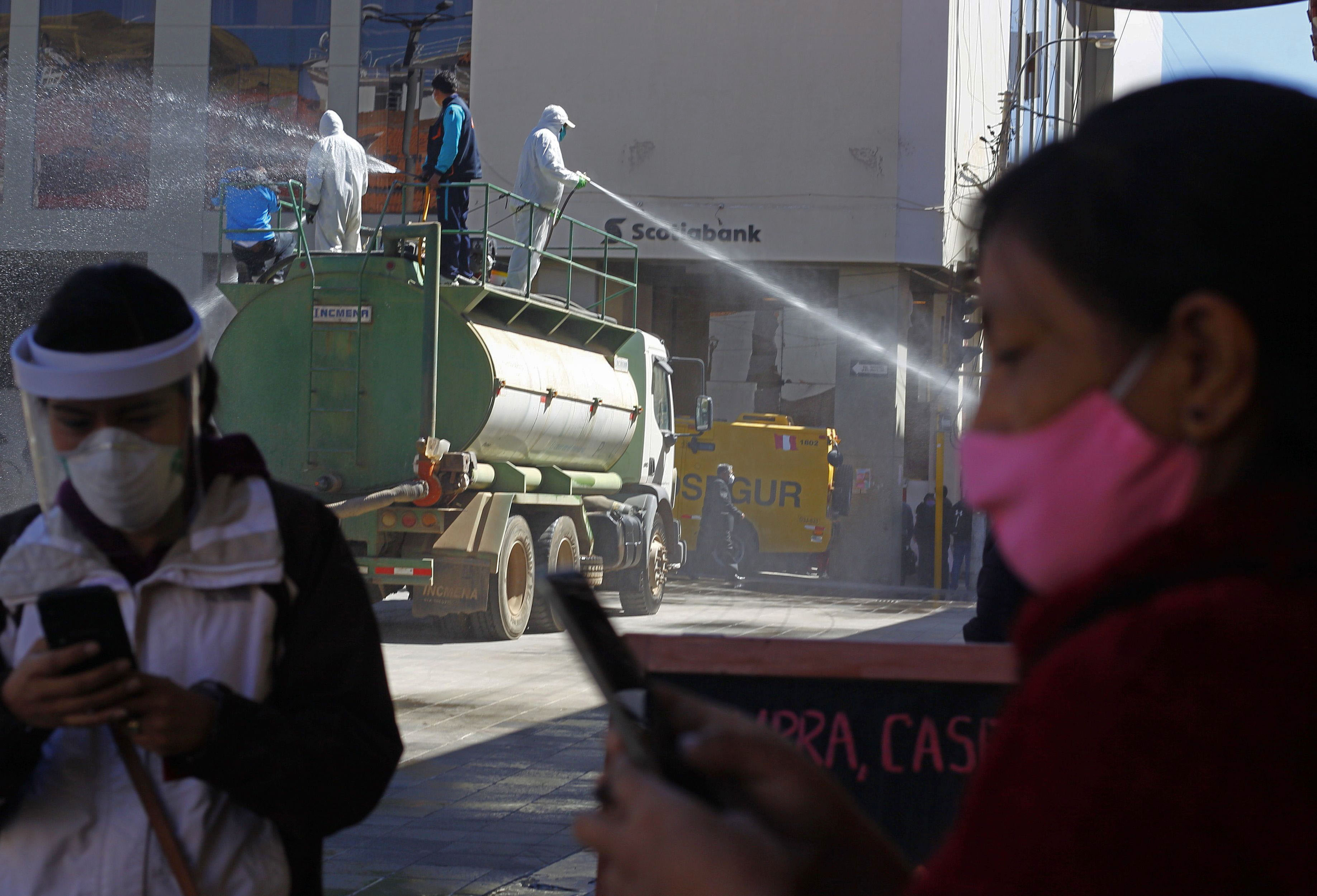 Workers disinfect streets in Puno, Peru, on July 17.