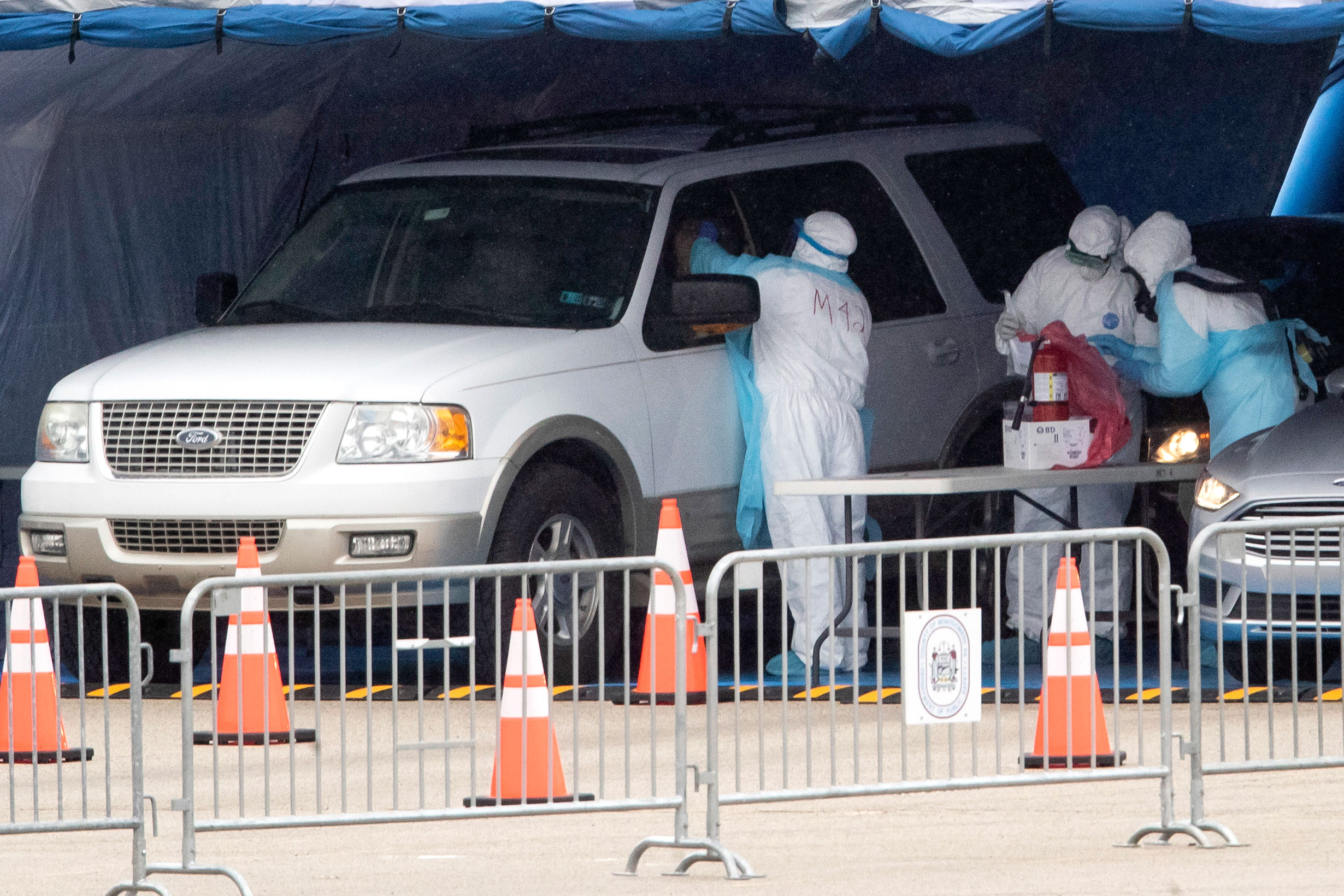 Medical workers perform a coronavirus test on driver at the Temple University Ambler campus in Ambler, Pennsylvania on March 25.