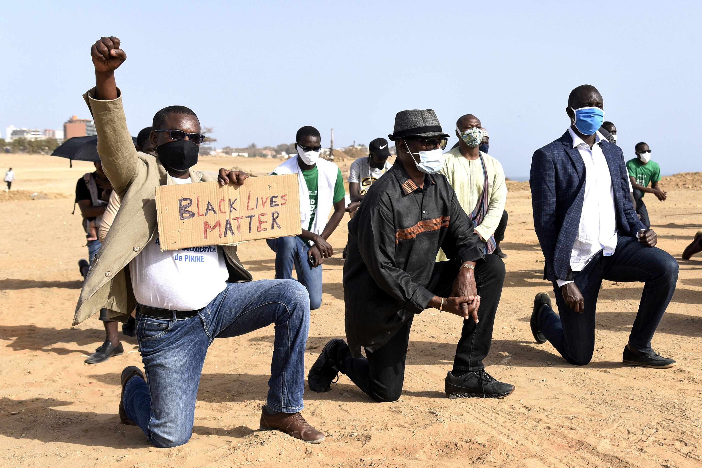 Protesters wearing face masks kneel in Dakar on June 9 during a rally in solidarity with the Black Lives Matter movement, and against racism and police brutality in the wake of the death of George Floyd.