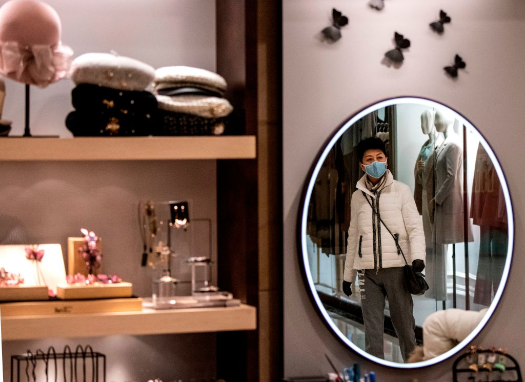 A woman wearing a protective face mask is reflected in a mirror as she walks inside a mall in Shanghai on February 8.